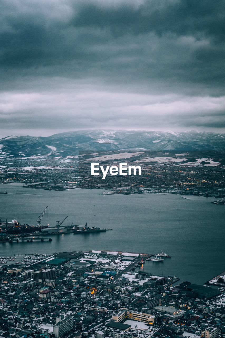 Aerial View Of Sea And Cityscape Against Cloudy Sky