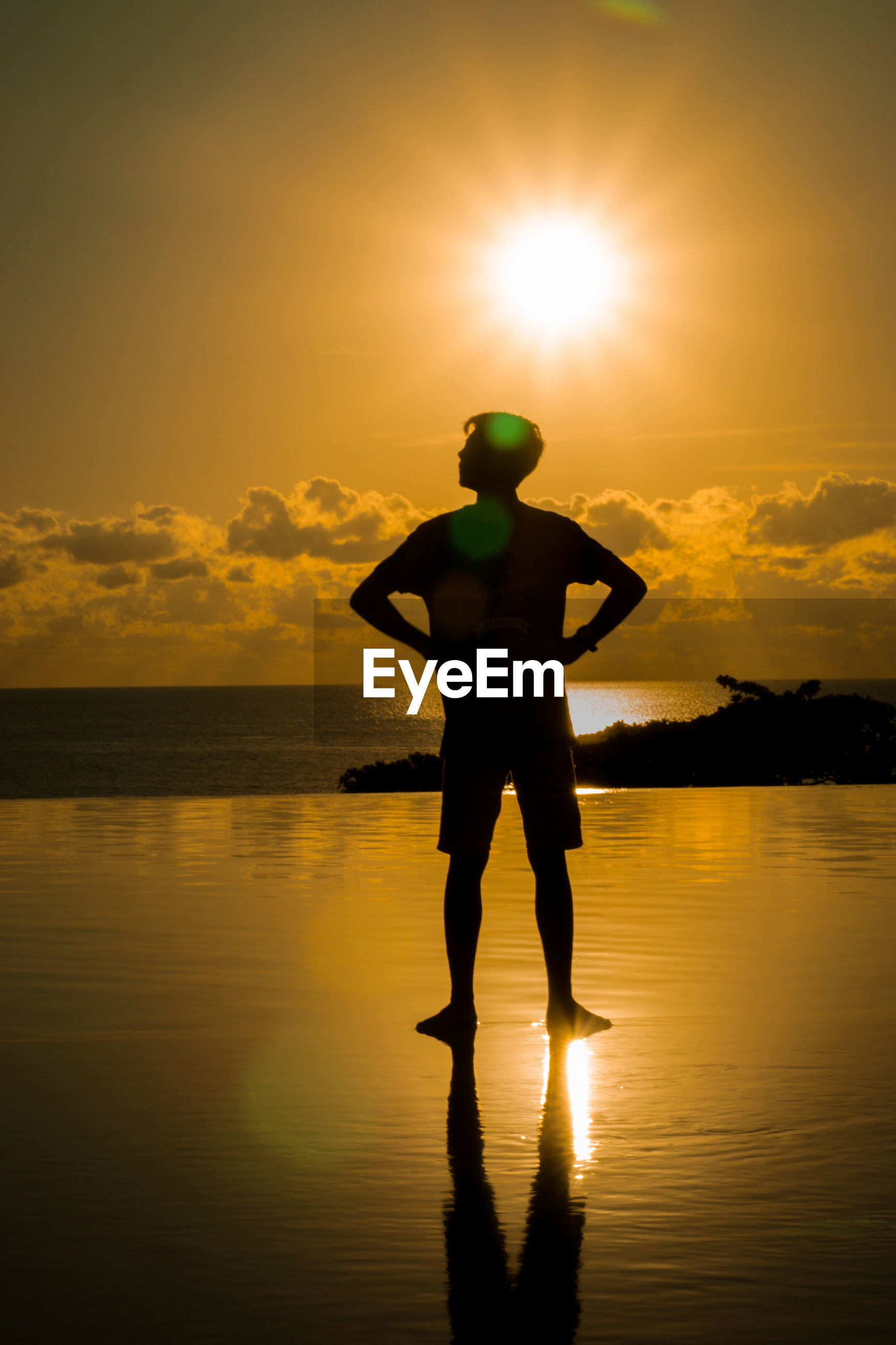 Silhouette man standing on infinity pool by sea against sky during sunset