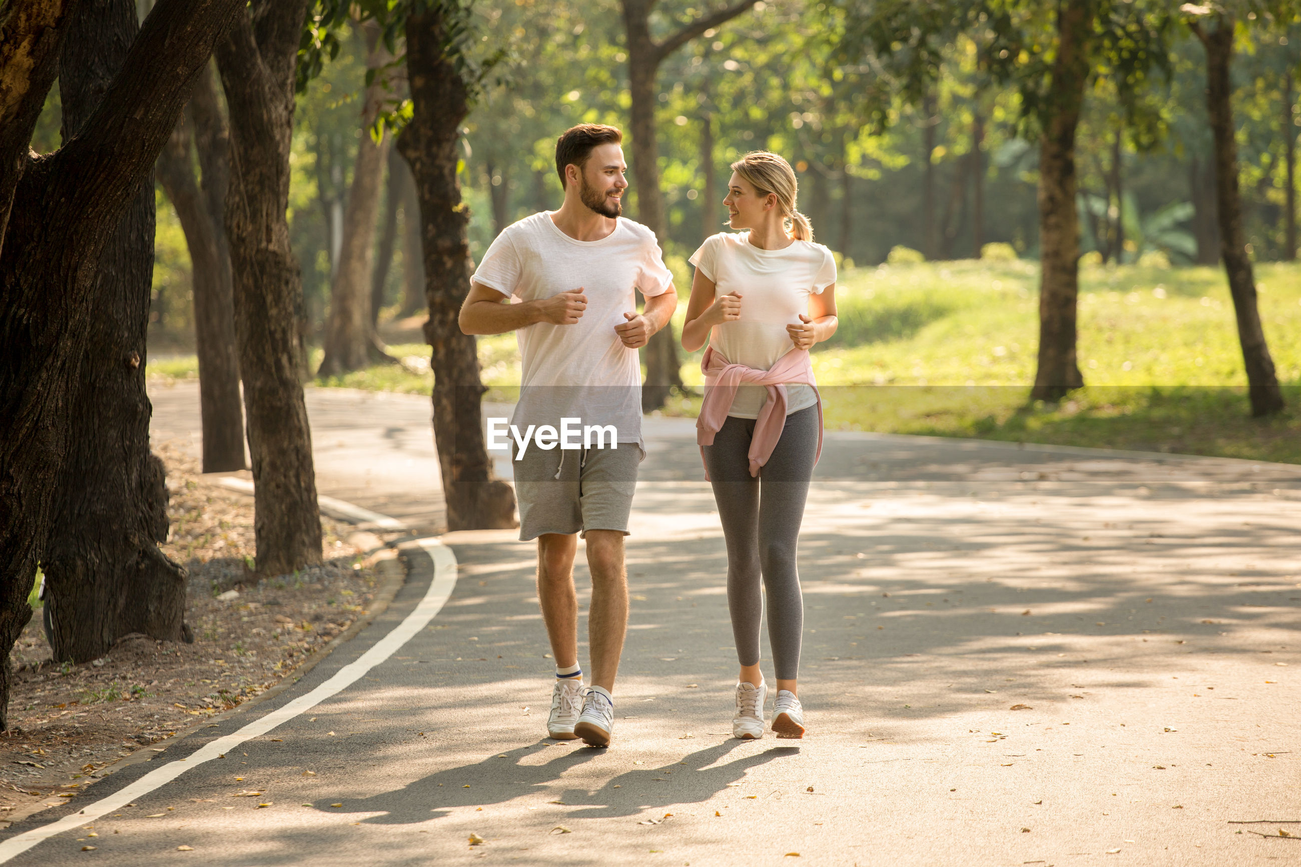 Full length of young couple running in park