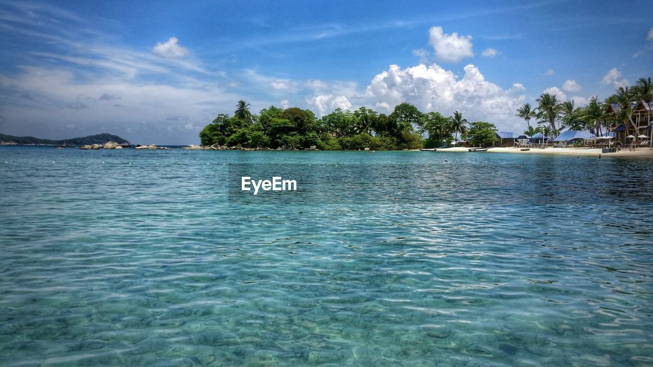 sky, water, sea, beauty in nature, nature, tranquility, scenics, waterfront, tranquil scene, rippled, cloud - sky, tree, outdoors, blue, no people, day, palm tree