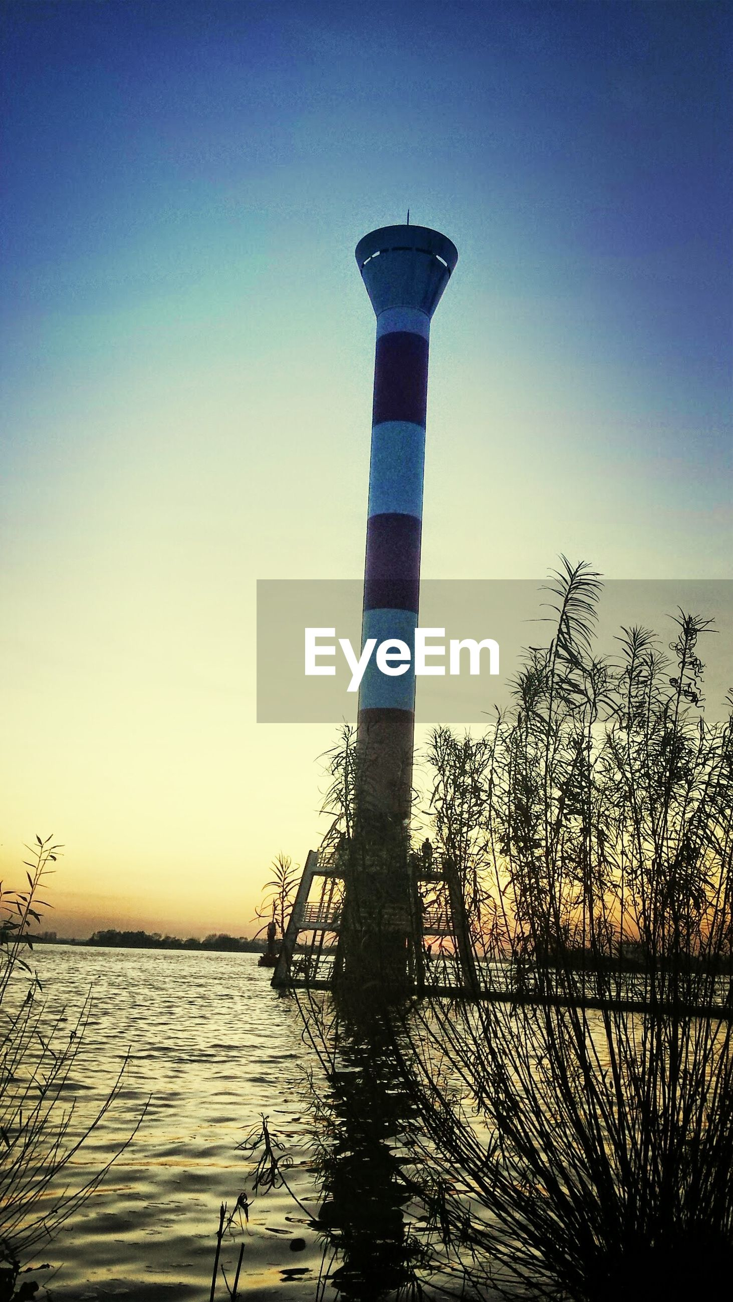 water, sea, clear sky, tranquility, sunset, blue, tranquil scene, nature, protection, horizon over water, scenics, beauty in nature, safety, copy space, guidance, lighthouse, sky, built structure, security, no people