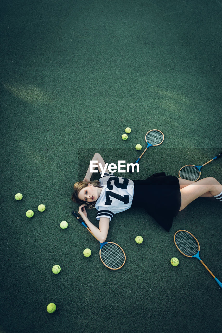 High angle view of tired young woman lying on court