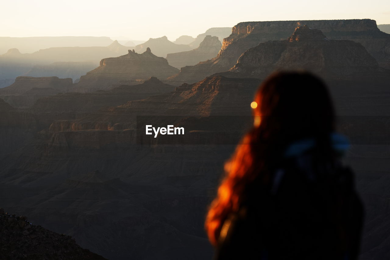 Rear view of woman standing at grand canyon during sunset