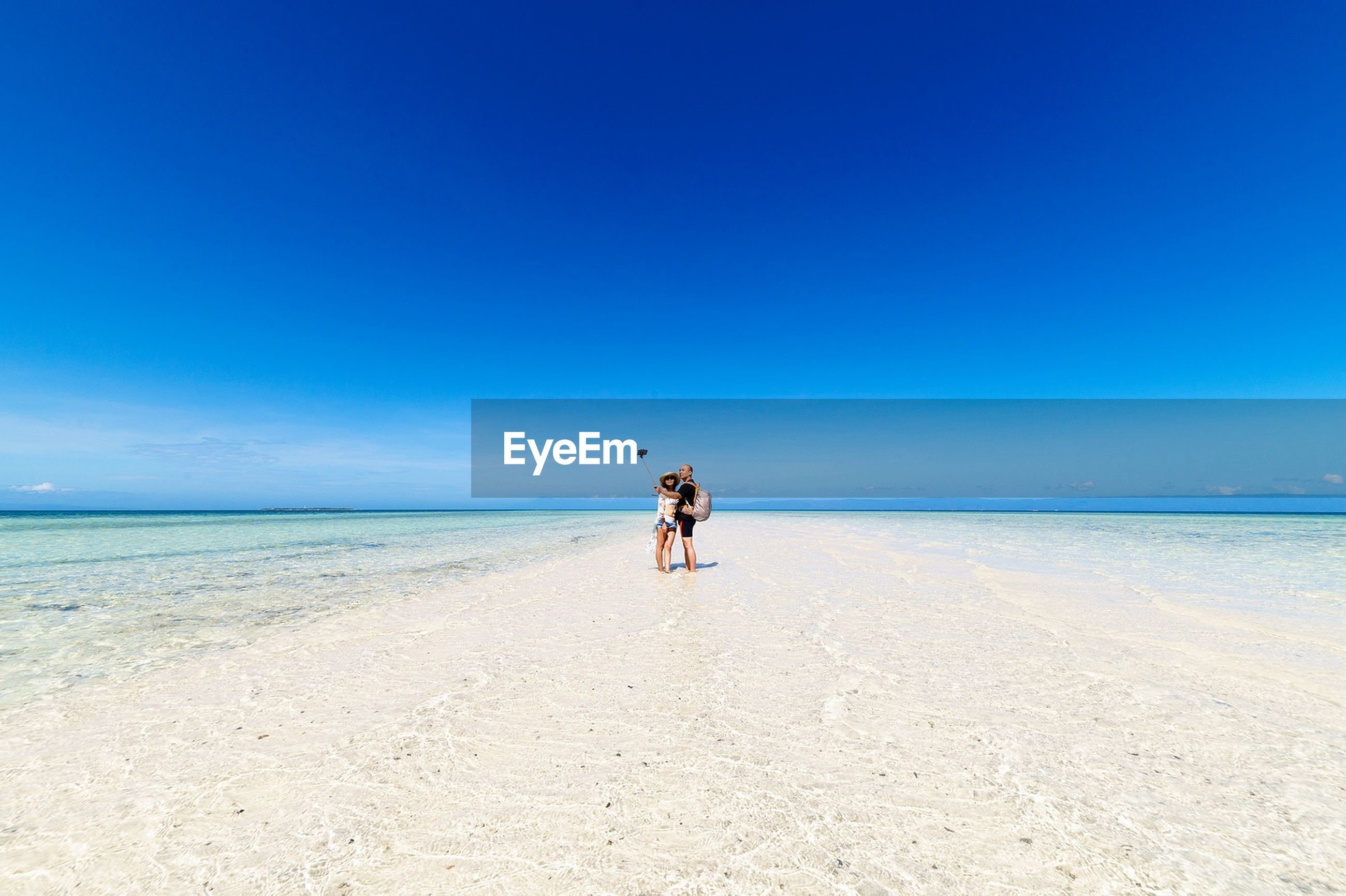 View of couple on beach against clear blue sky