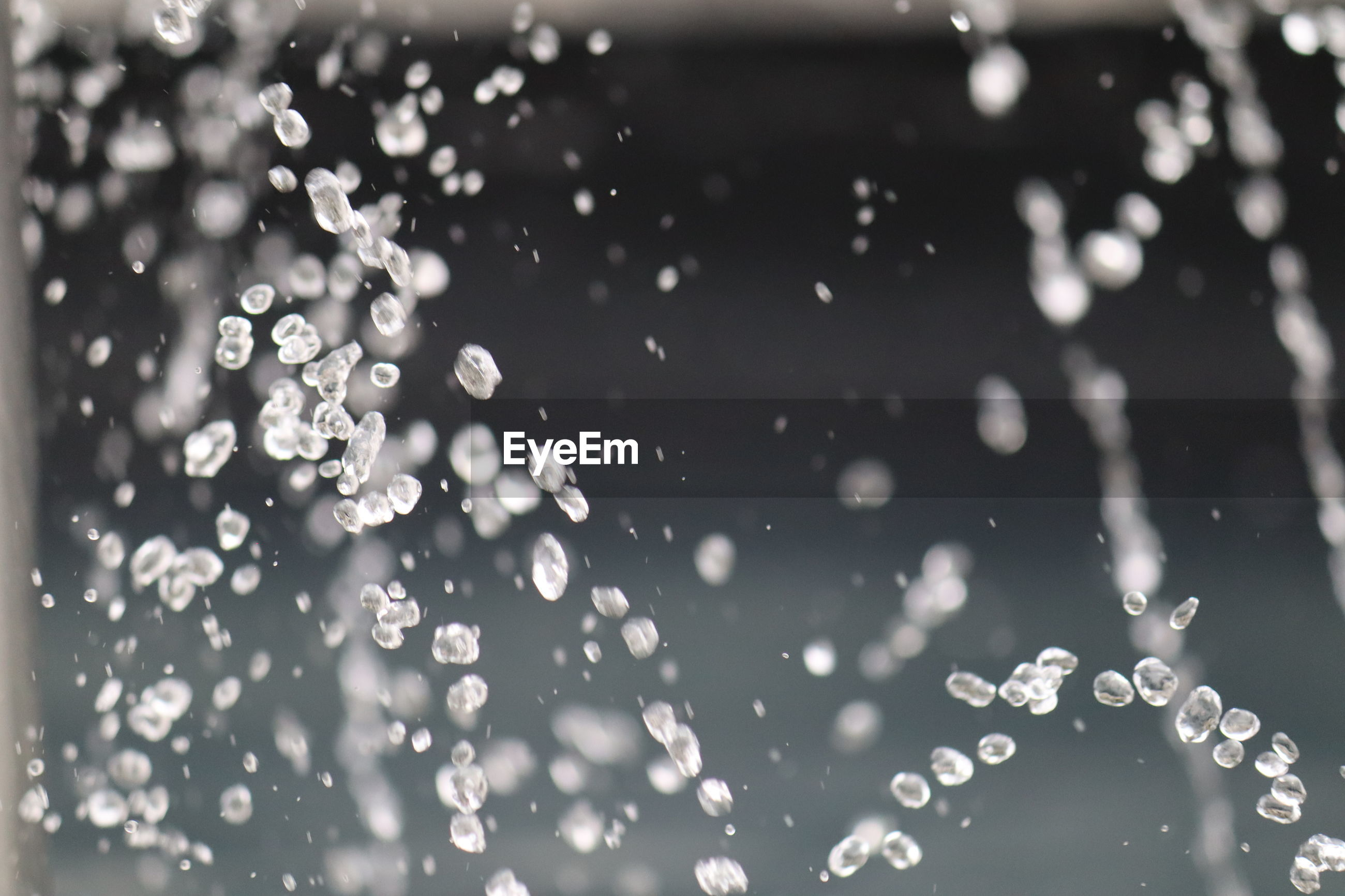 DEFOCUSED IMAGE OF WATER DROPS ON BLACK BACKGROUND