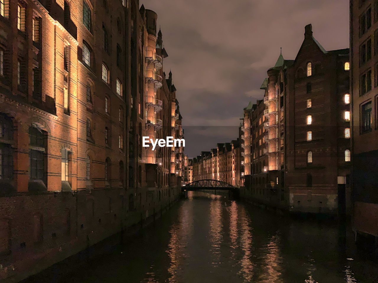 CANAL AMIDST BUILDINGS AGAINST SKY IN CITY AT DUSK