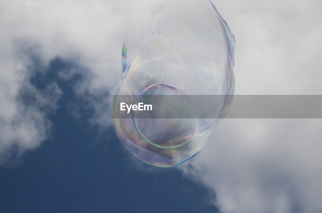 vulnerability, fragility, bubble, mid-air, cloud - sky, transparent, soap sud, sky, nature, no people, low angle view, close-up, flying, day, focus on foreground, sphere, shape, outdoors, multi colored, reflection, lightweight