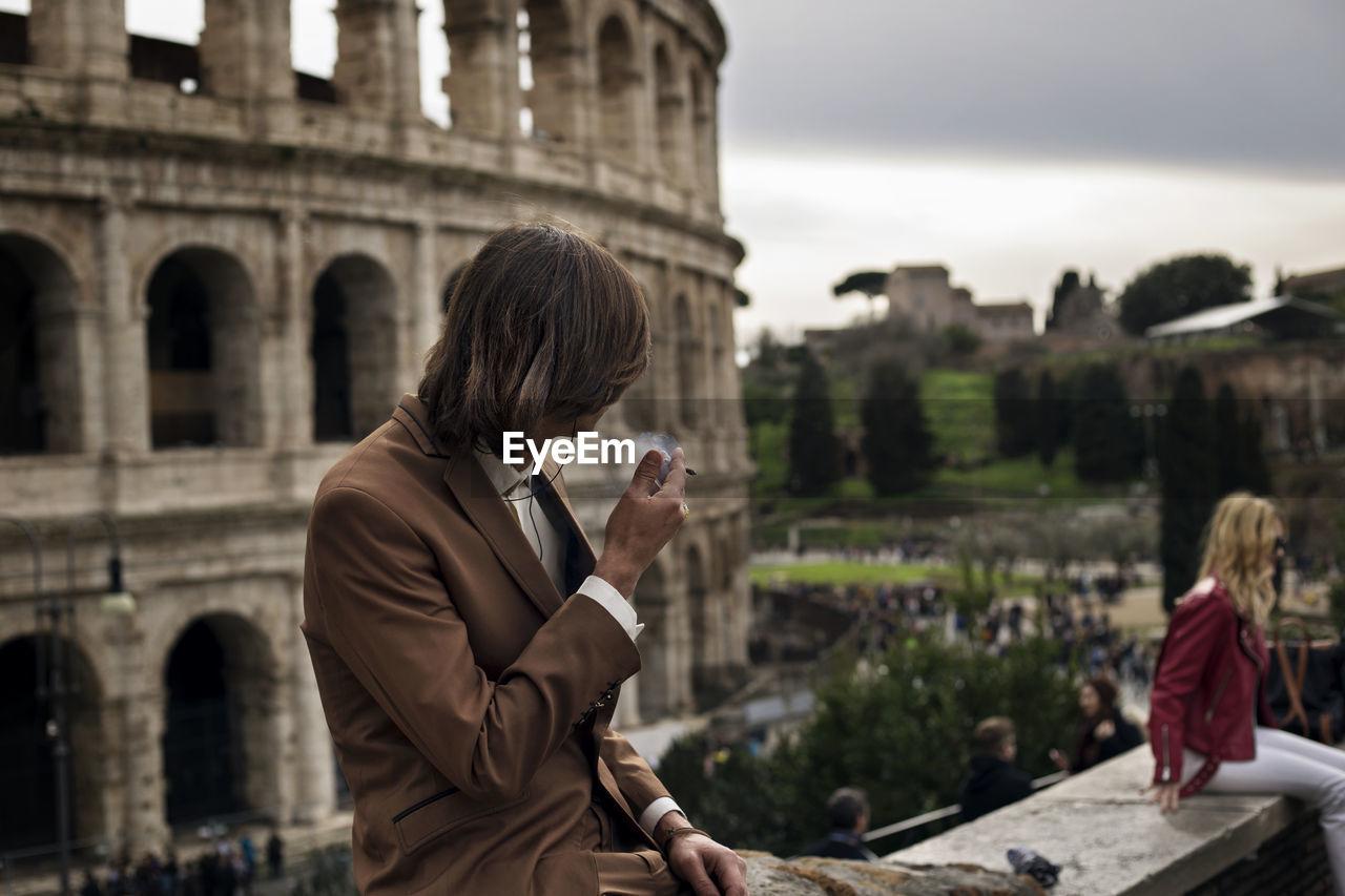 Man smoking cigarette against coliseum