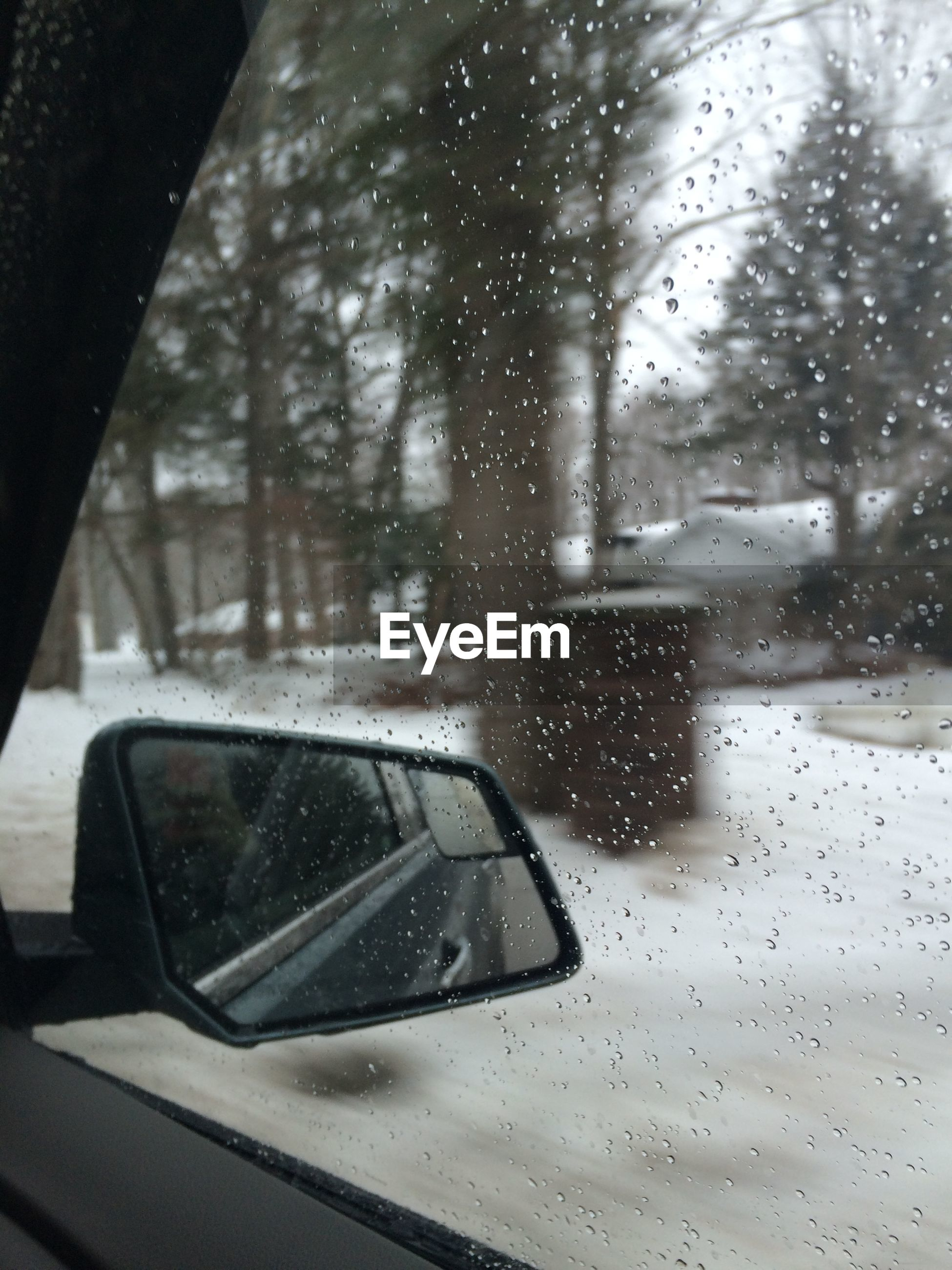 Close-up of side-view mirror seen through wet window