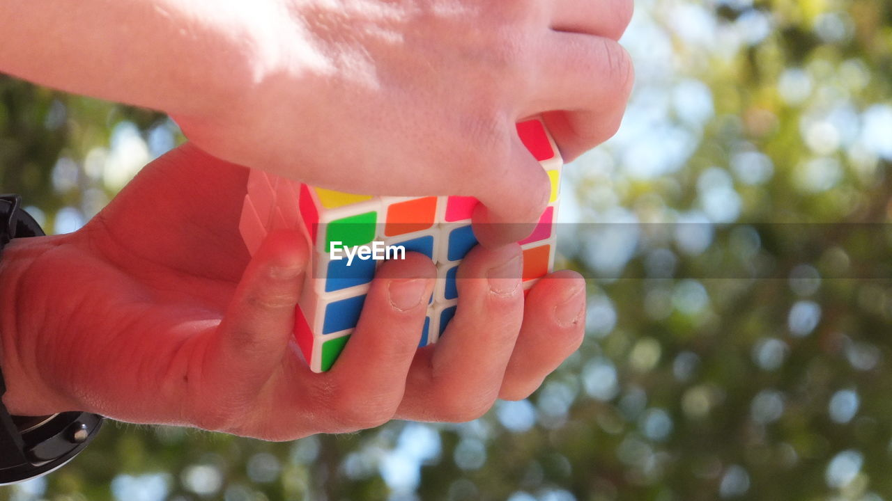 Extreme Close Up Of Hand Holding Colorful Cube