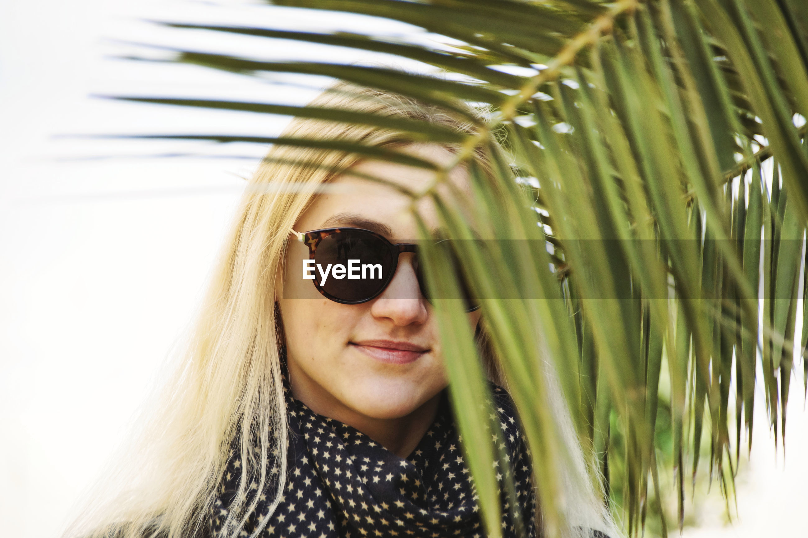 Portrait of young woman wearing sunglasses standing by plants in park