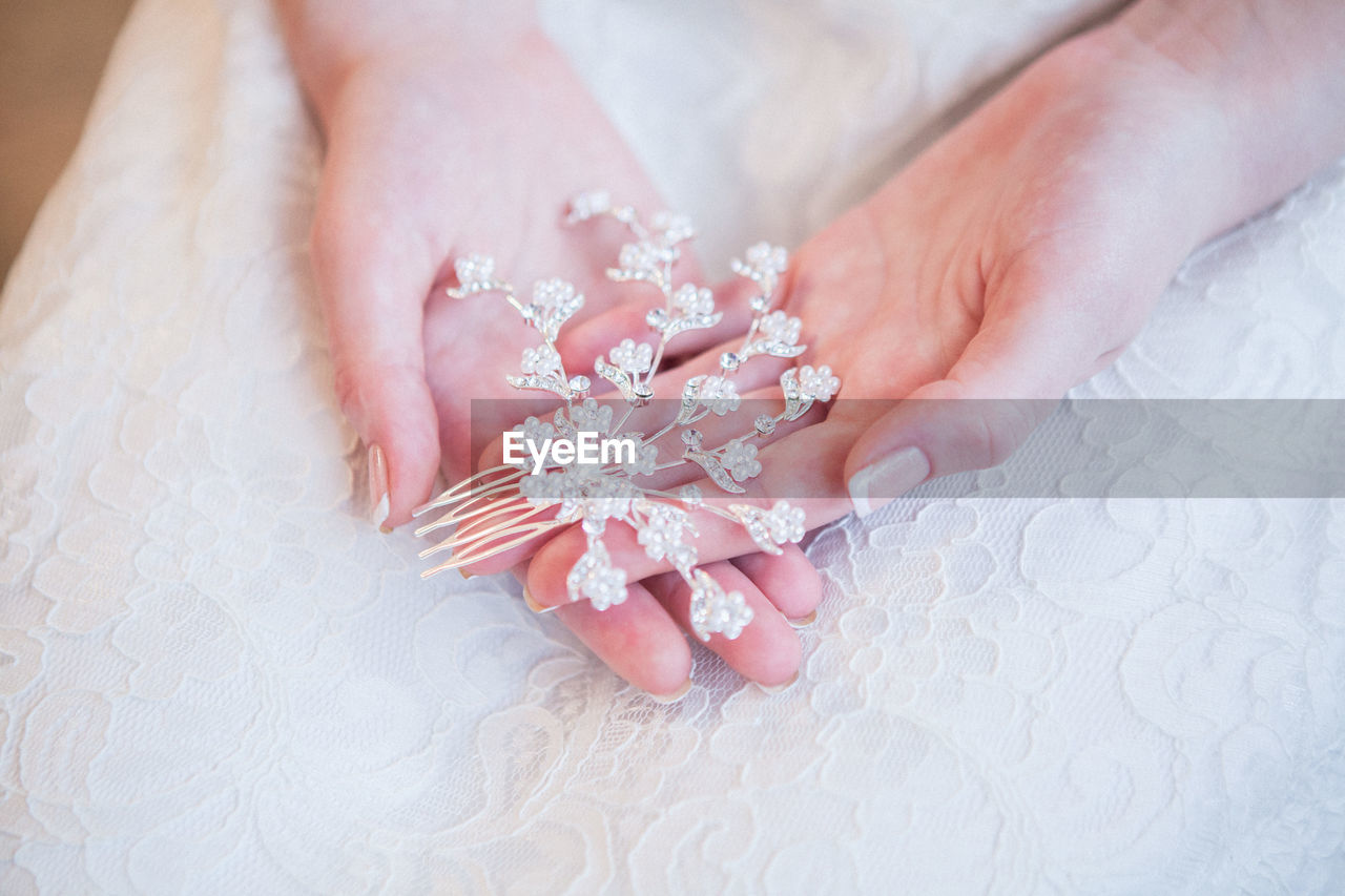 Midsection of bride holding jewelry on table
