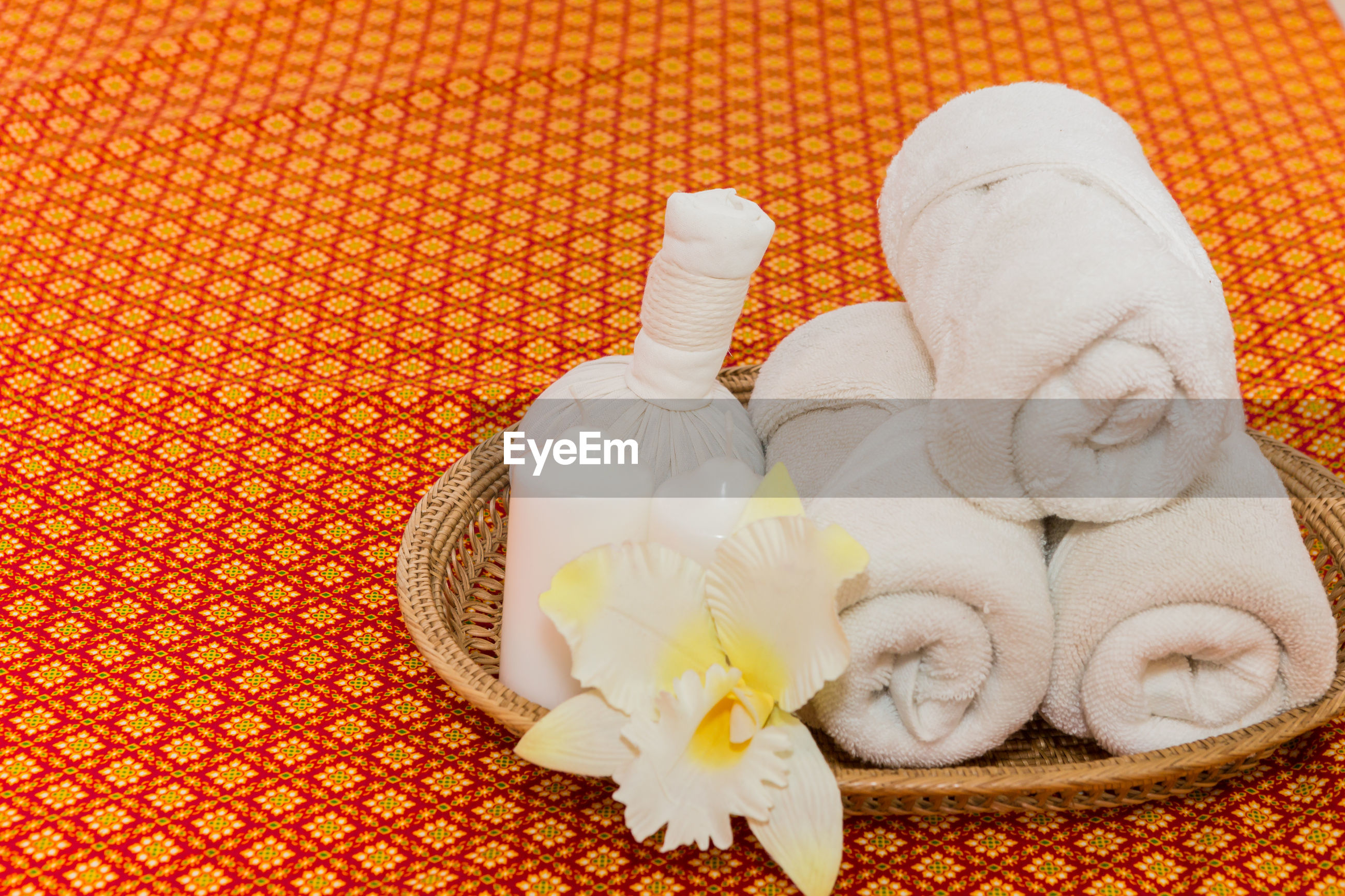 Close-up of towels and flowers on mattress