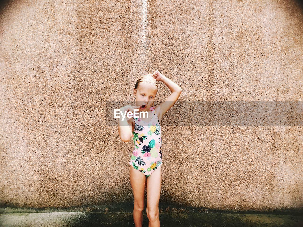 Girl wearing swimwear while taking shower against wall