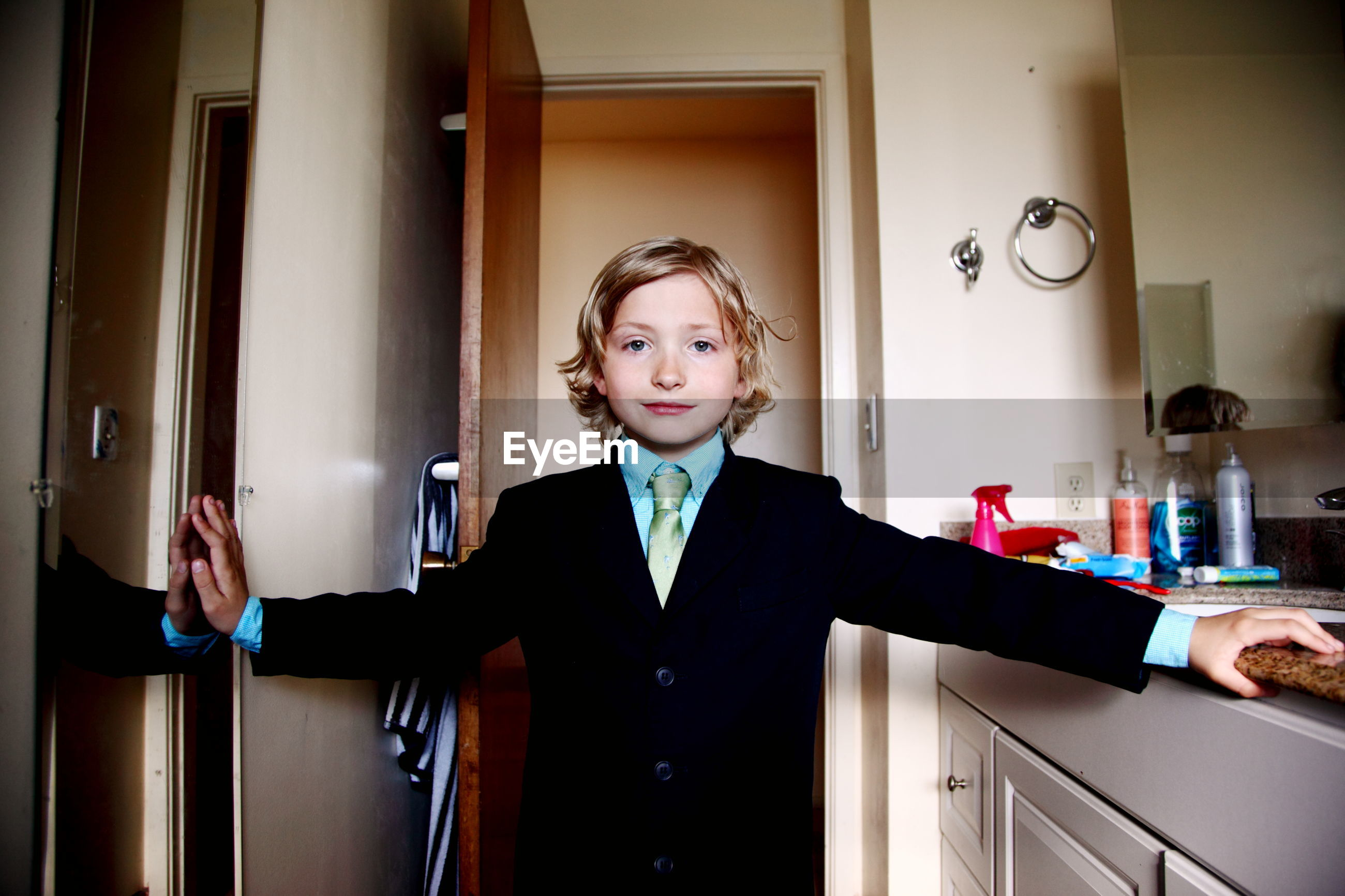 Close-up portrait of boy wearing suit standing against door at home
