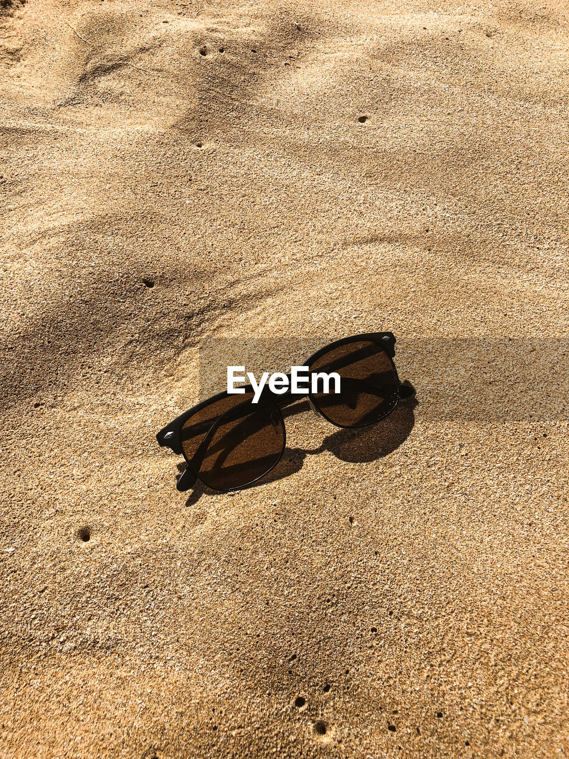 HIGH ANGLE VIEW OF BUTTERFLY ON SANDY BEACH