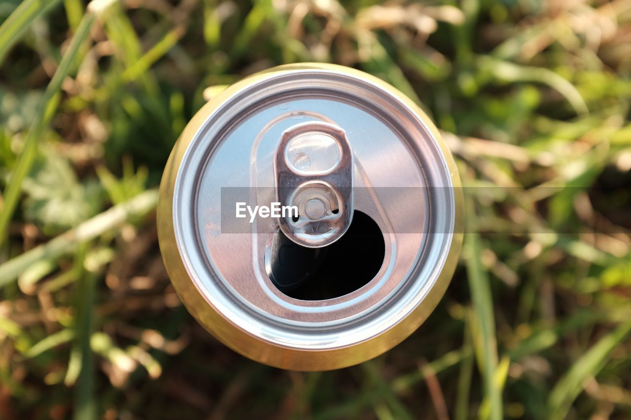 Directly above shot of open beer can on grass