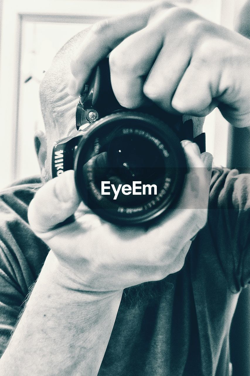 human hand, holding, one person, real people, human body part, photographing, photography themes, technology, camera - photographic equipment, leisure activity, men, indoors, lifestyles, photographer, close-up, wristwatch, day, digital single-lens reflex camera, adult, people, adults only