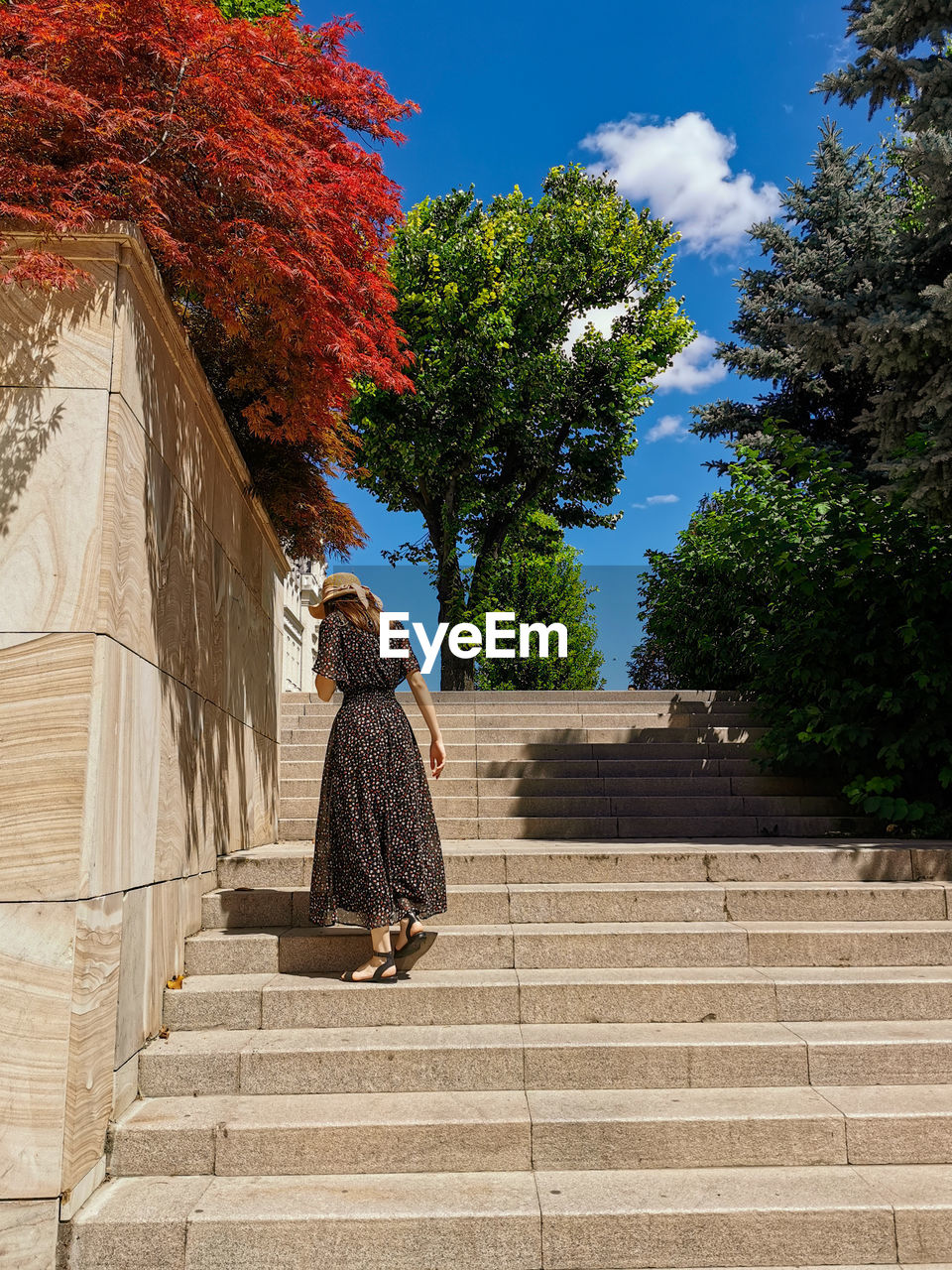 REAR VIEW OF WOMAN WALKING ON STAIRCASE AGAINST BUILDING