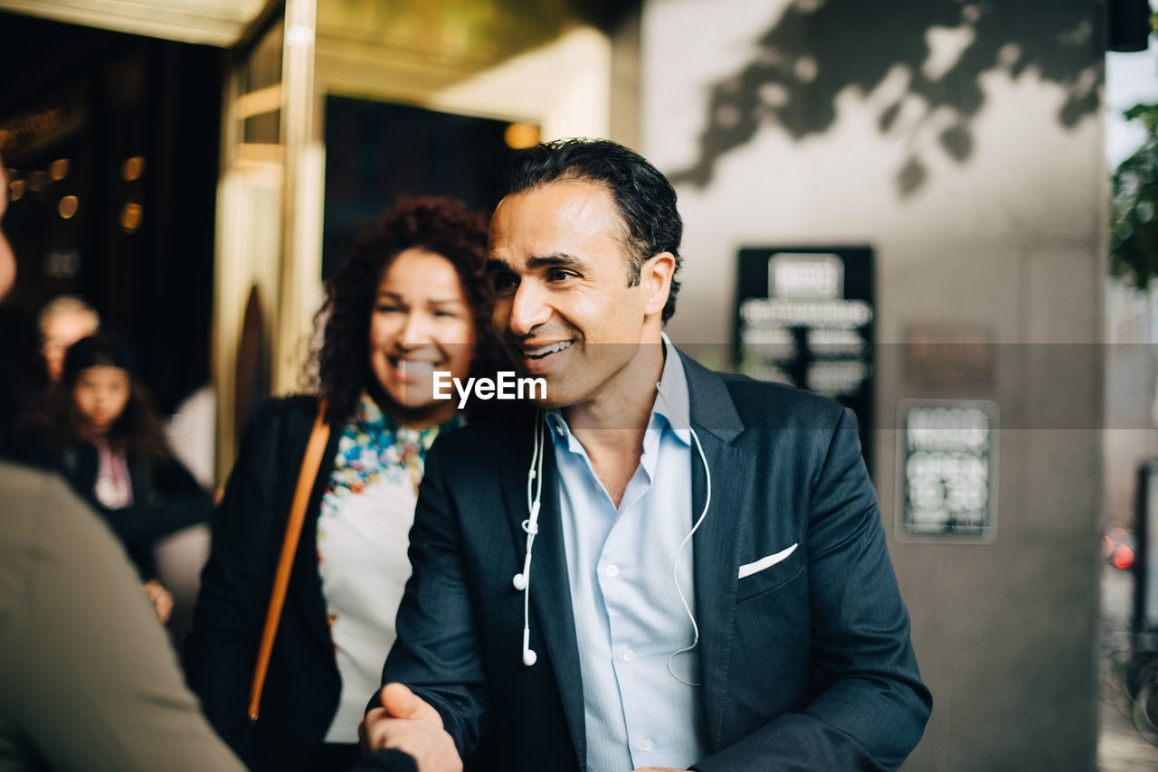 Smiling mature businessman greeting businesswoman while standing by female colleague against building