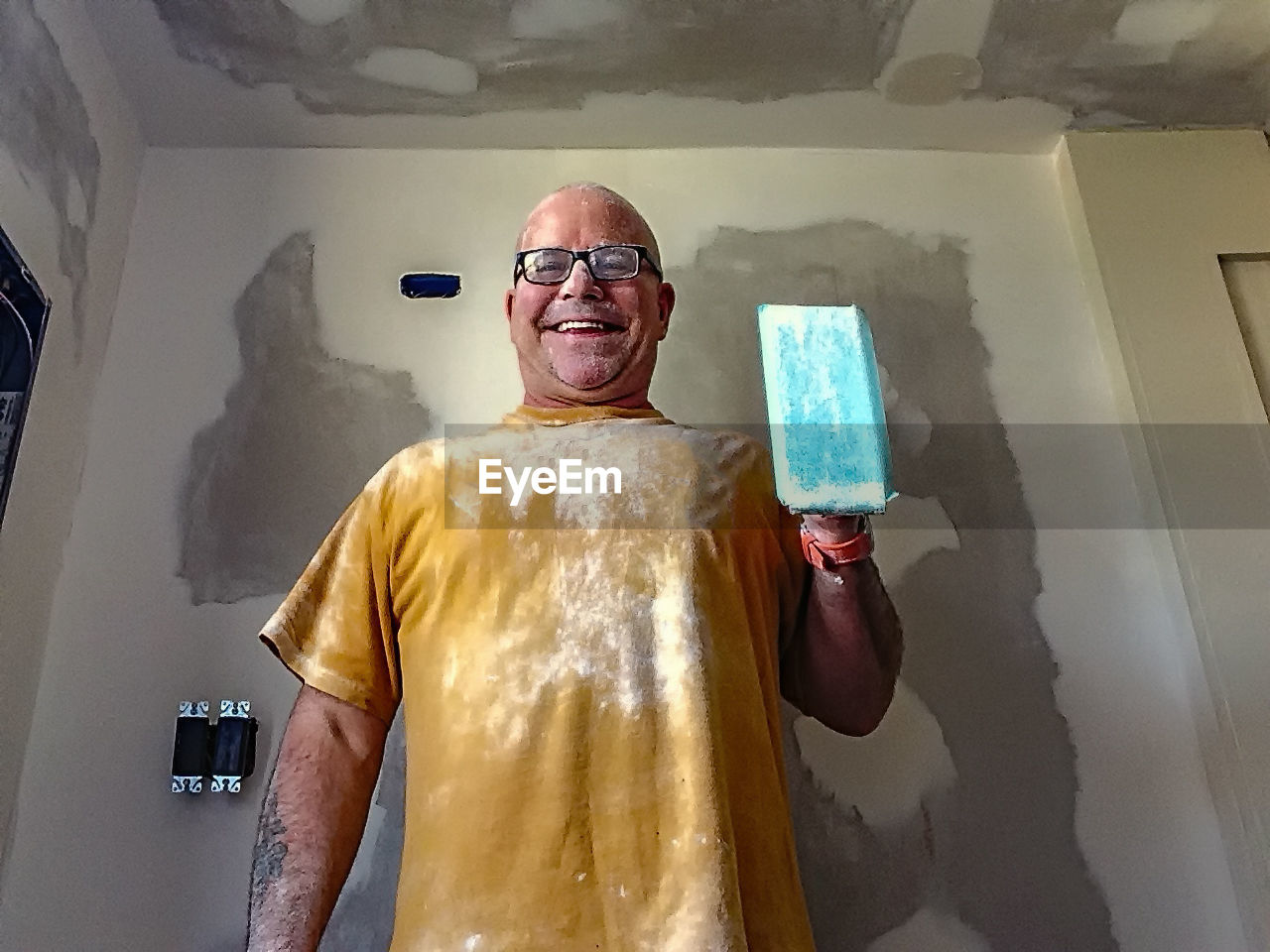 Low angle view of happy worker standing against wall