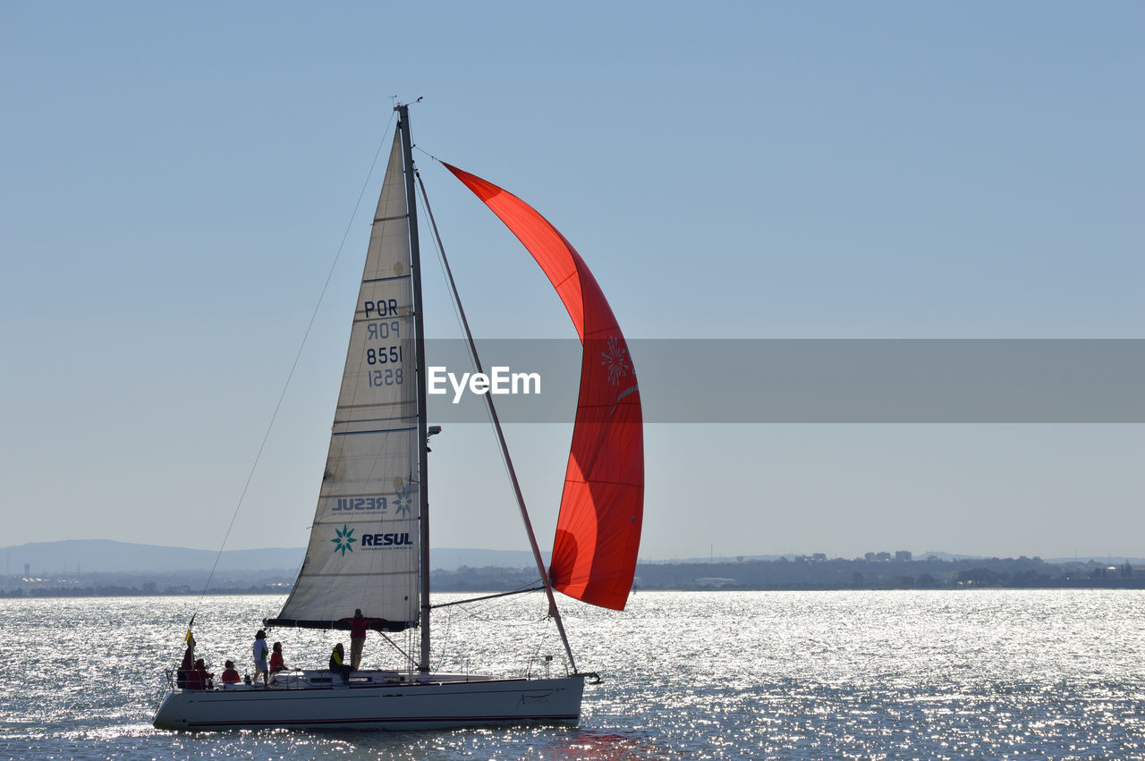 People On Sailboat Sailing In Sea At Sunny Day
