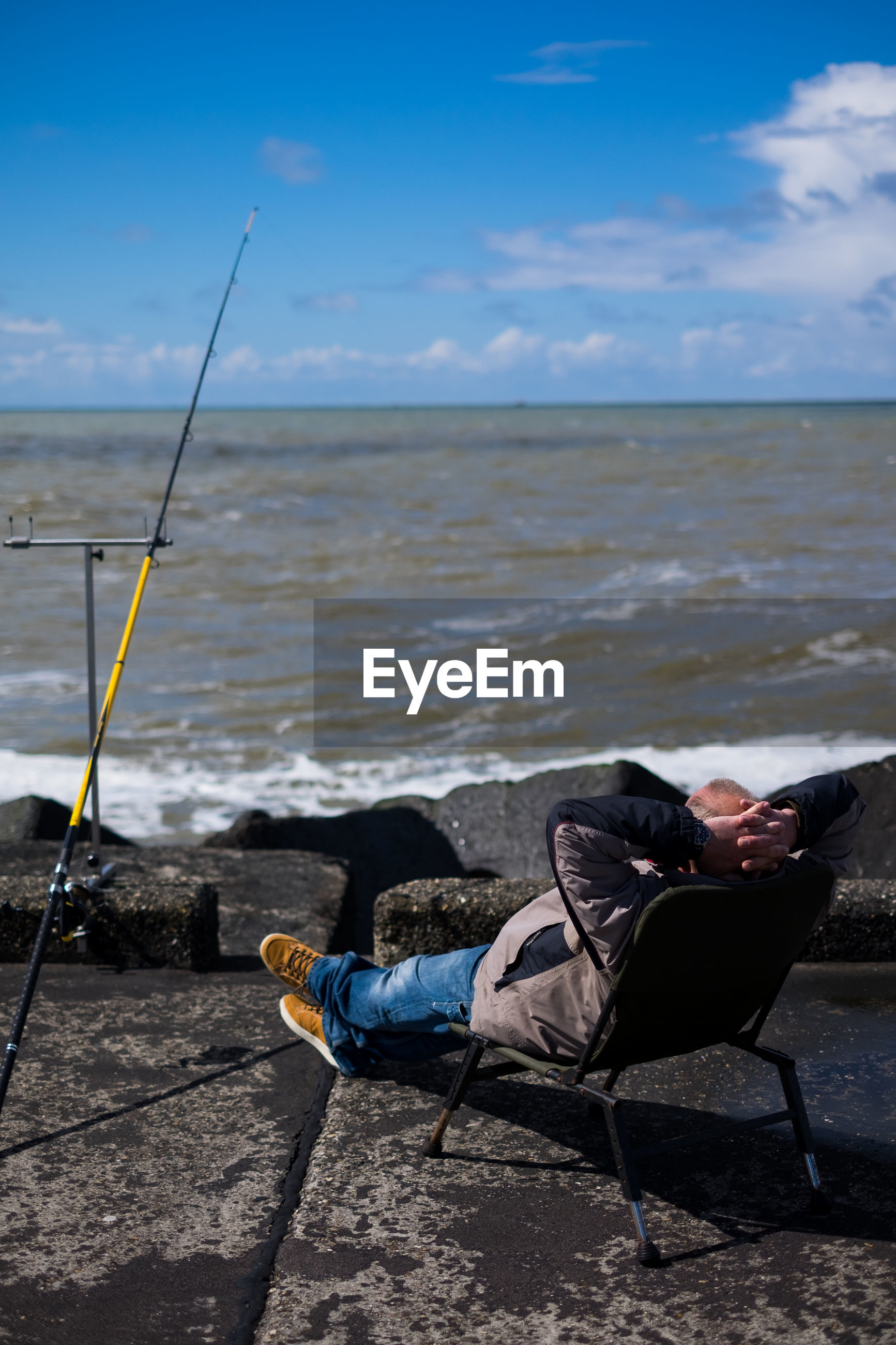 Rear view of man sitting on chair by fishing rod at rocky sea shore