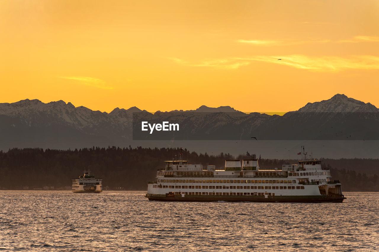 Ferry boats sailing in sea against orange sky