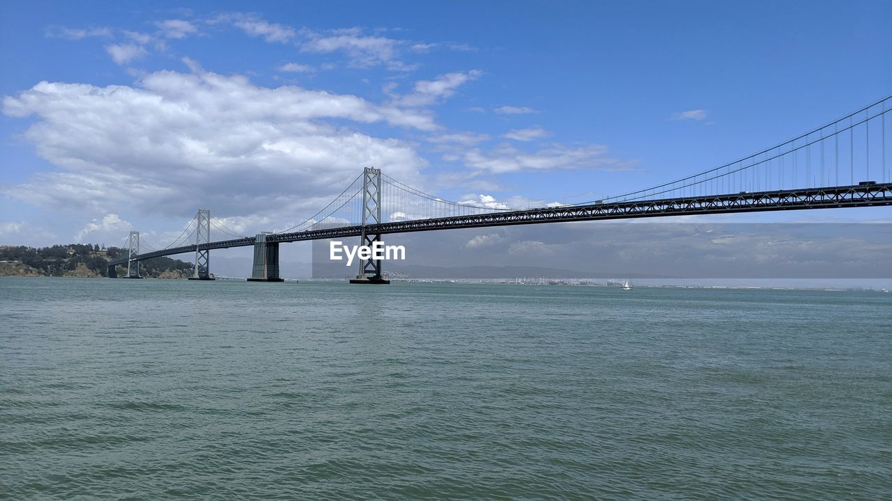 water, sky, bridge, built structure, architecture, connection, cloud - sky, bridge - man made structure, waterfront, engineering, transportation, nature, suspension bridge, sea, travel destinations, day, travel, beauty in nature, outdoors, bay, long