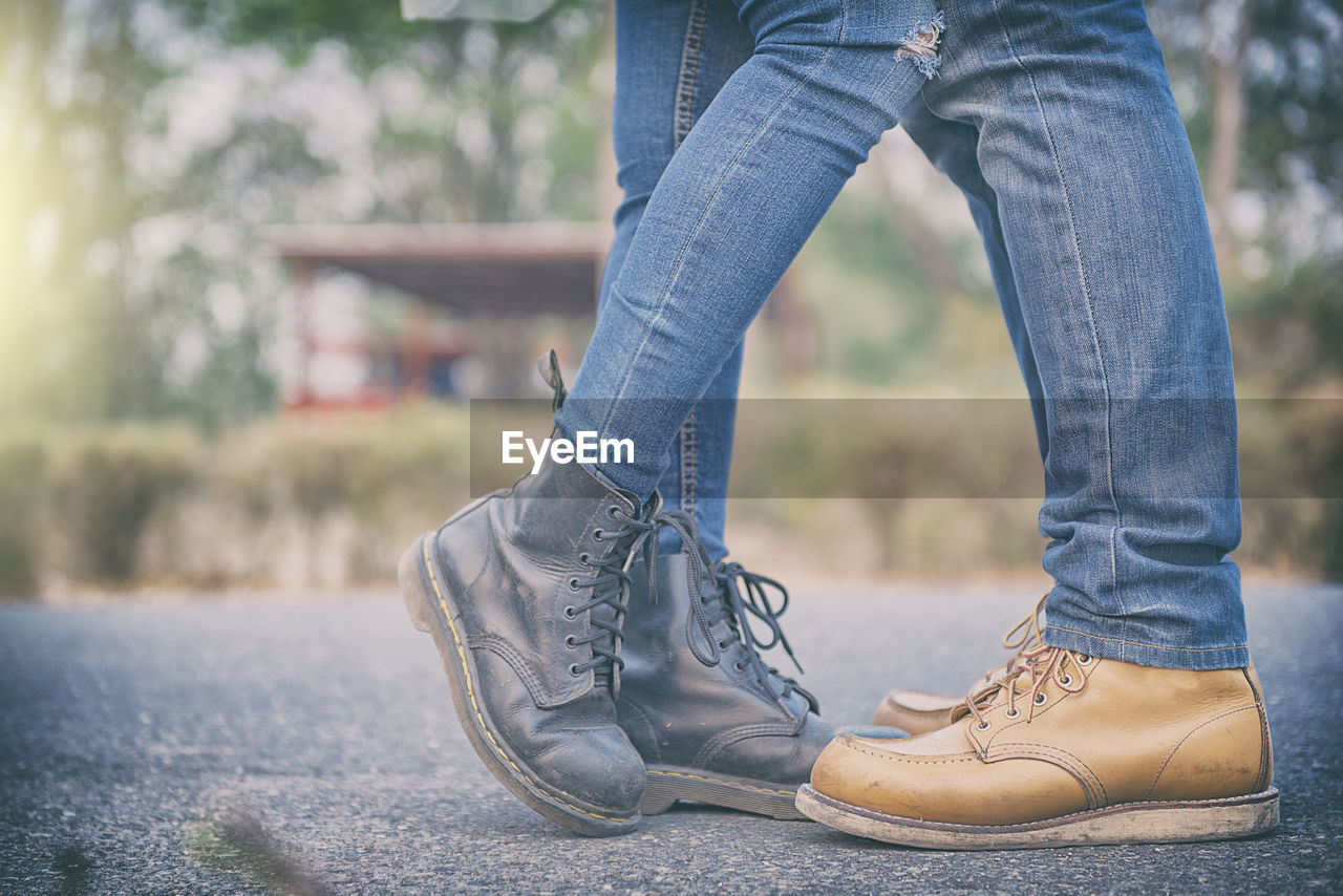 Low section of couple wearing shoes while standing on road