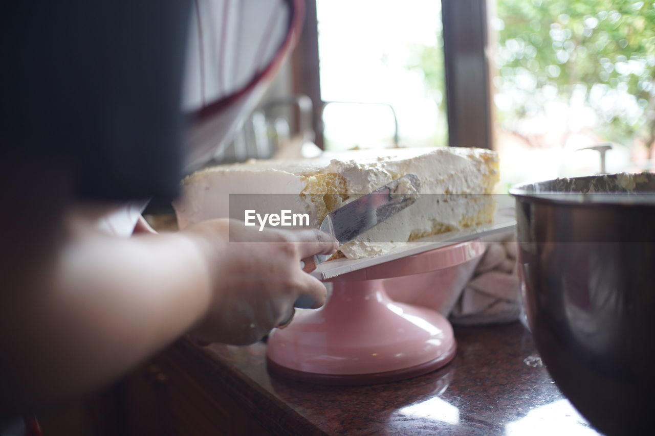 food and drink, food, hand, human hand, indoors, freshness, sweet food, real people, human body part, sweet, dessert, close-up, occupation, preparation, holding, working, one person, table, selective focus, temptation, preparing food, chef