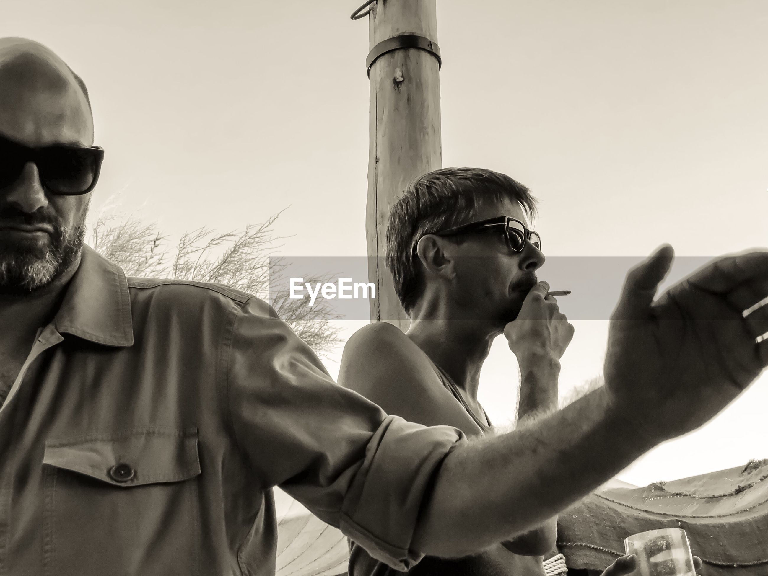 Man smoking cigarette with friend in foreground