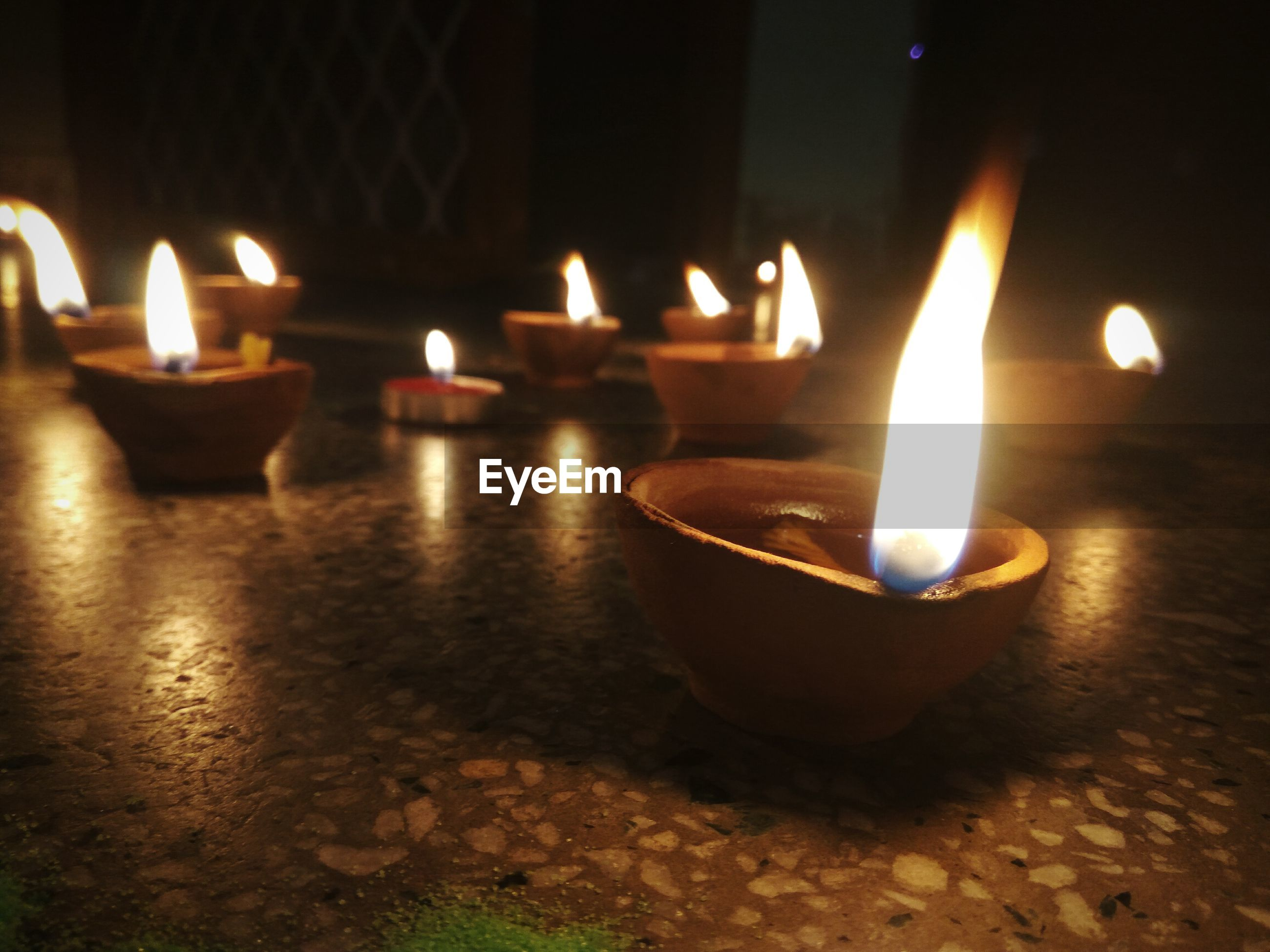 Close-up of lit diyas in darkroom