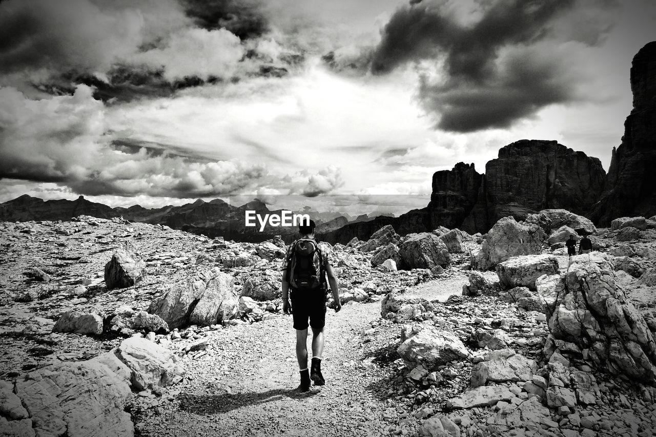 Rear view of man walking on pathway amidst rocks against cloudy sky