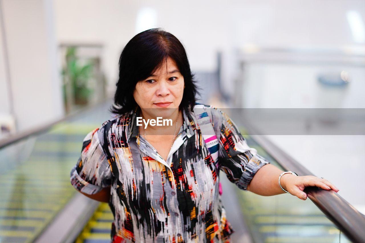 Woman Standing On Escalator In Mall