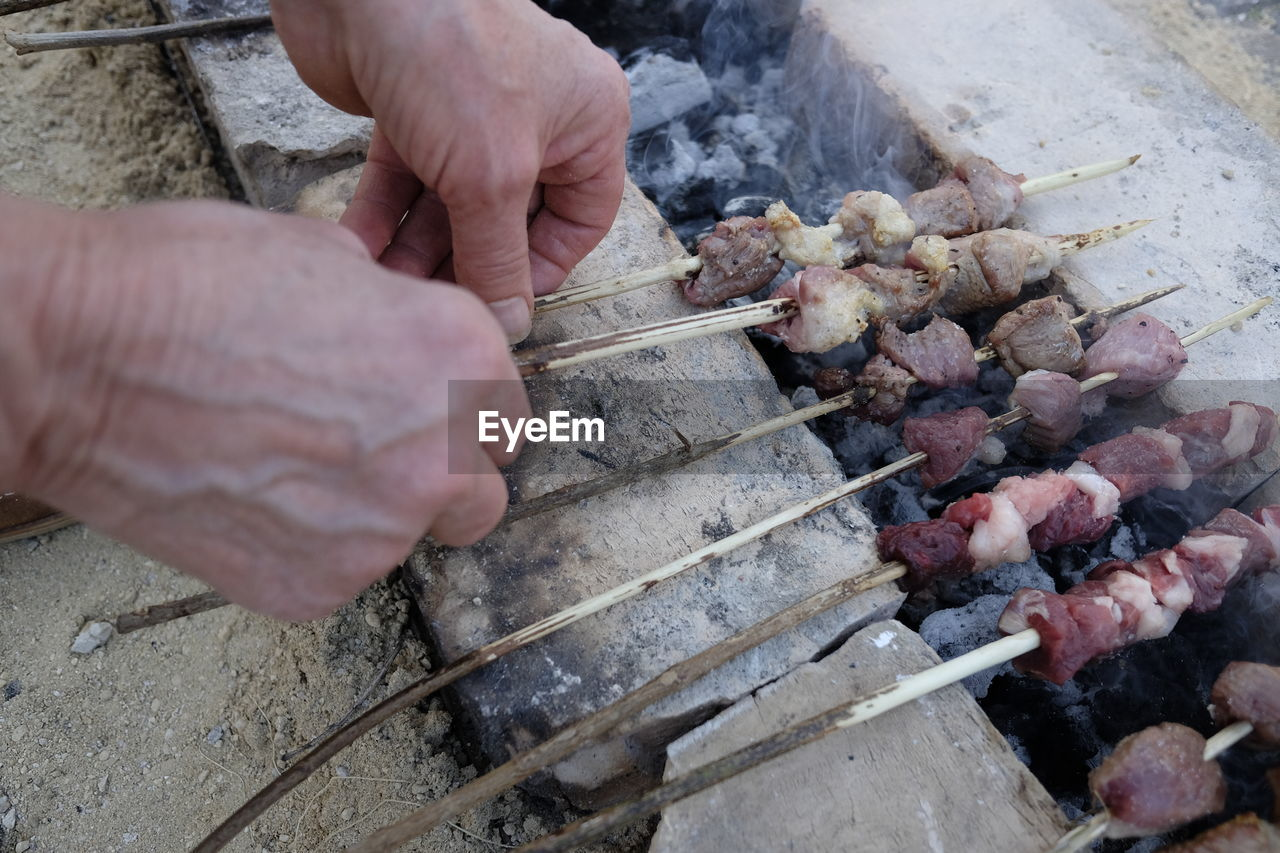 High angle view of man cooking meat skewers on barbecue