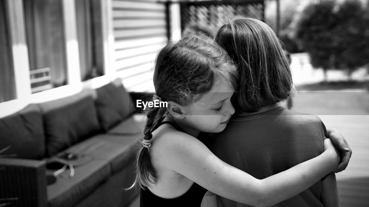 Side View Of Girl Embracing Sibling