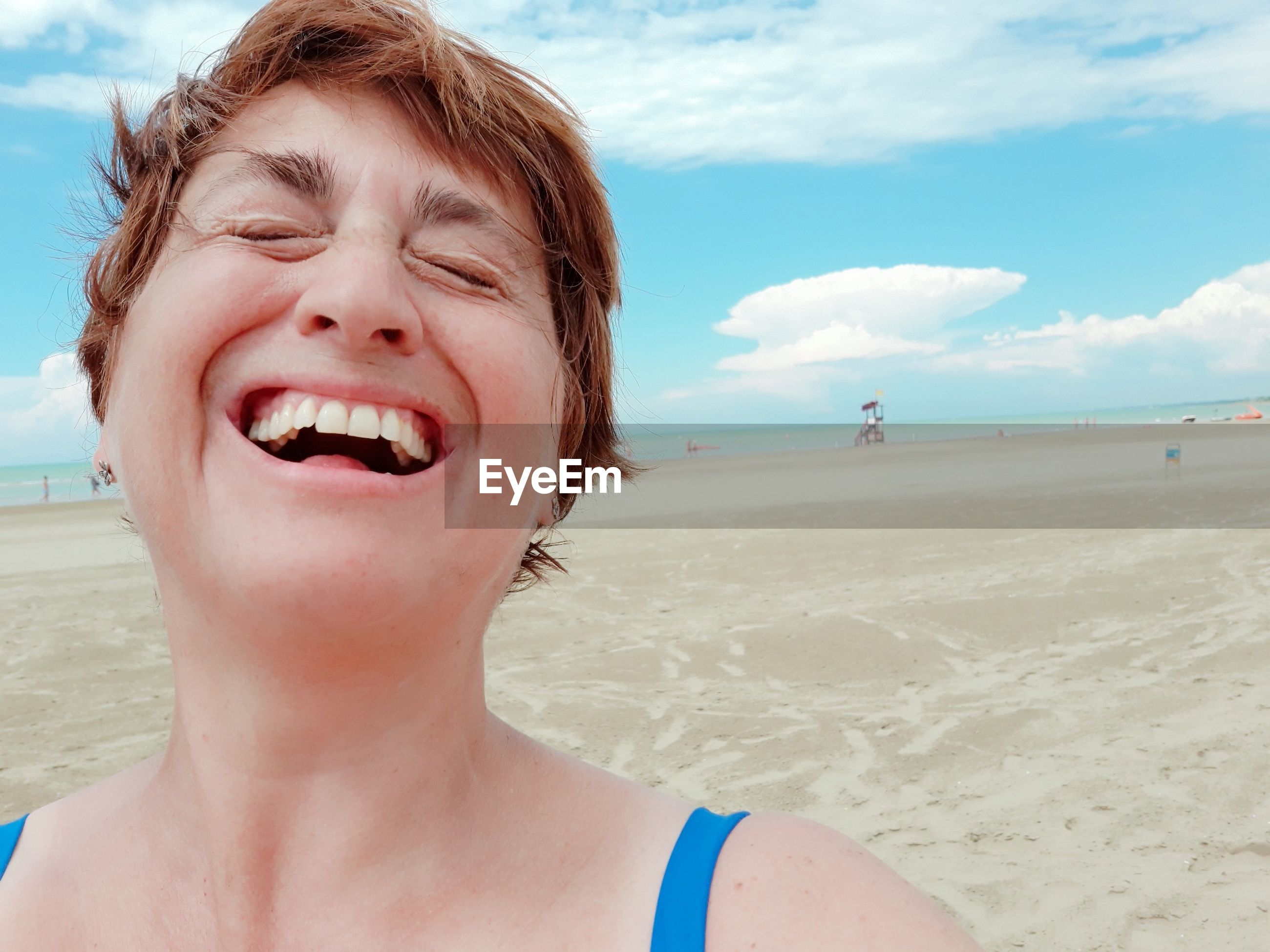 Close-up of woman laughing while standing at beach against sky