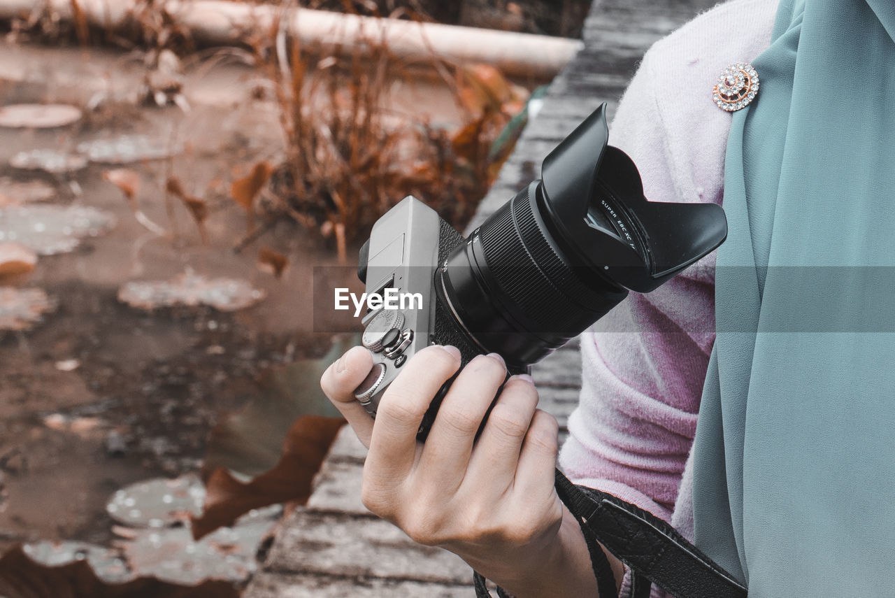 Midsection of man holding camera outdoors
