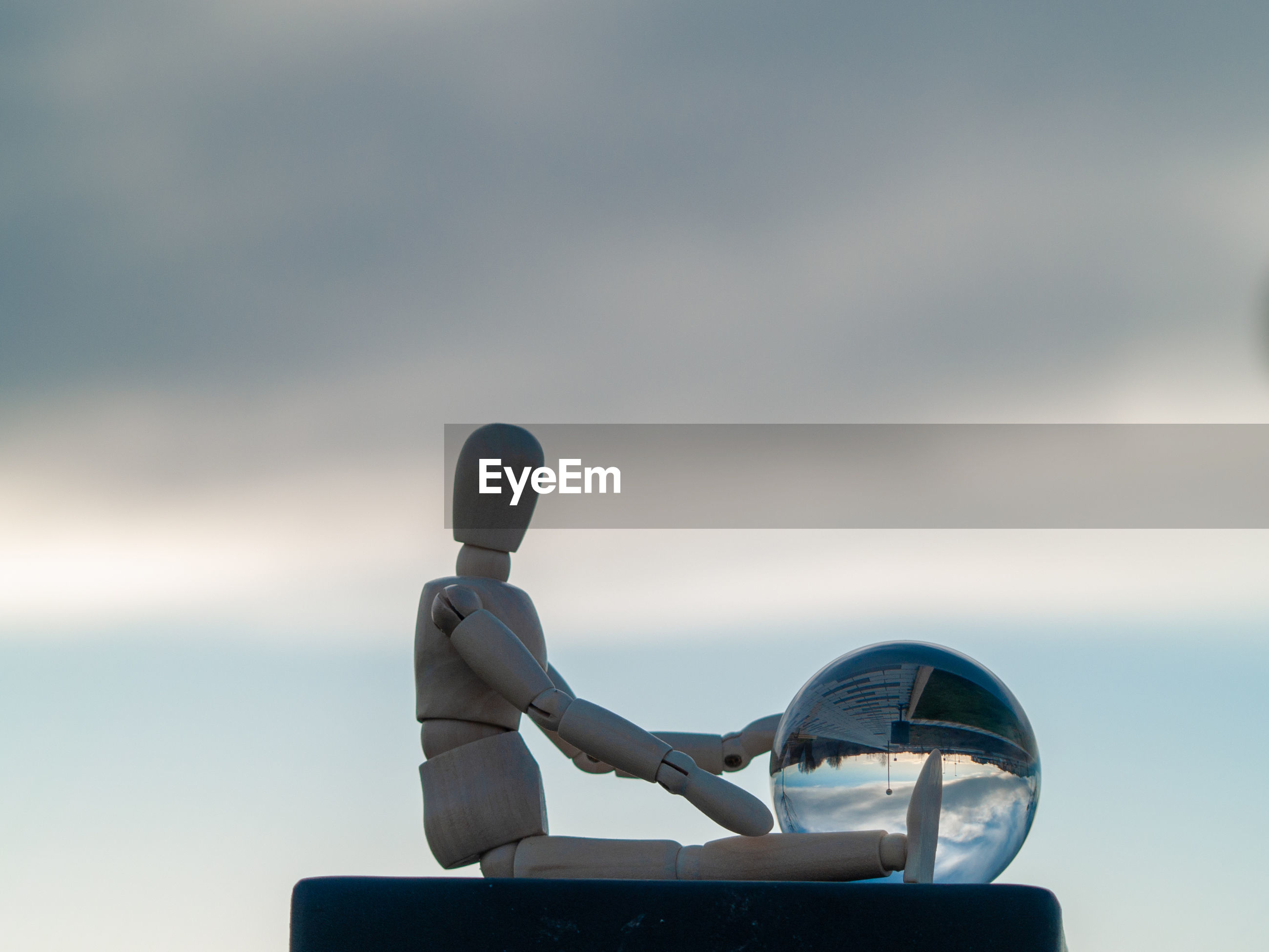 Close-up of figurine with crystal ball against cloudy sky