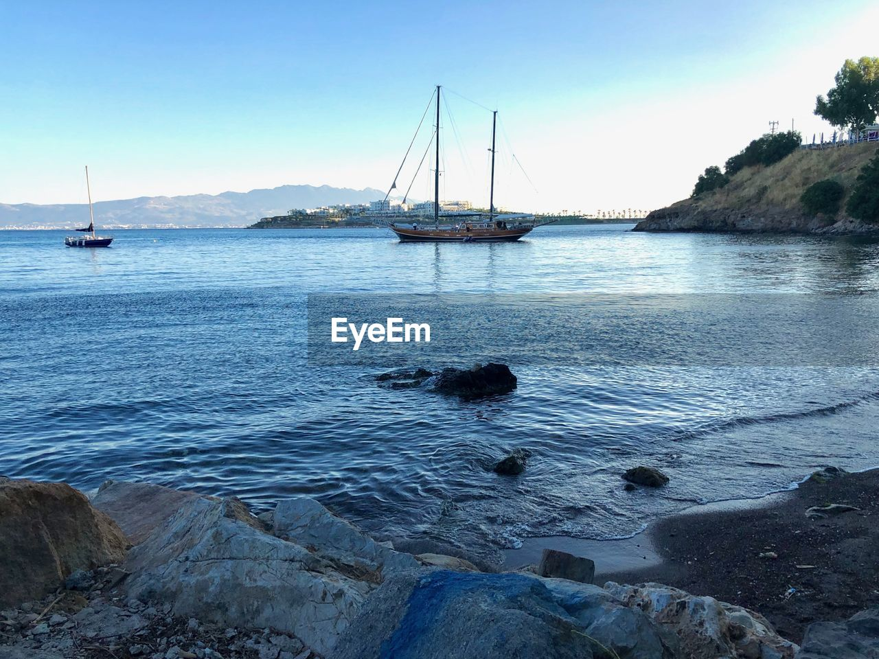 water, nautical vessel, sea, transportation, mode of transportation, sky, sailboat, rock, solid, rock - object, nature, beauty in nature, tranquil scene, scenics - nature, tranquility, pole, mast, beach, day, no people, outdoors, bay, yacht, marina