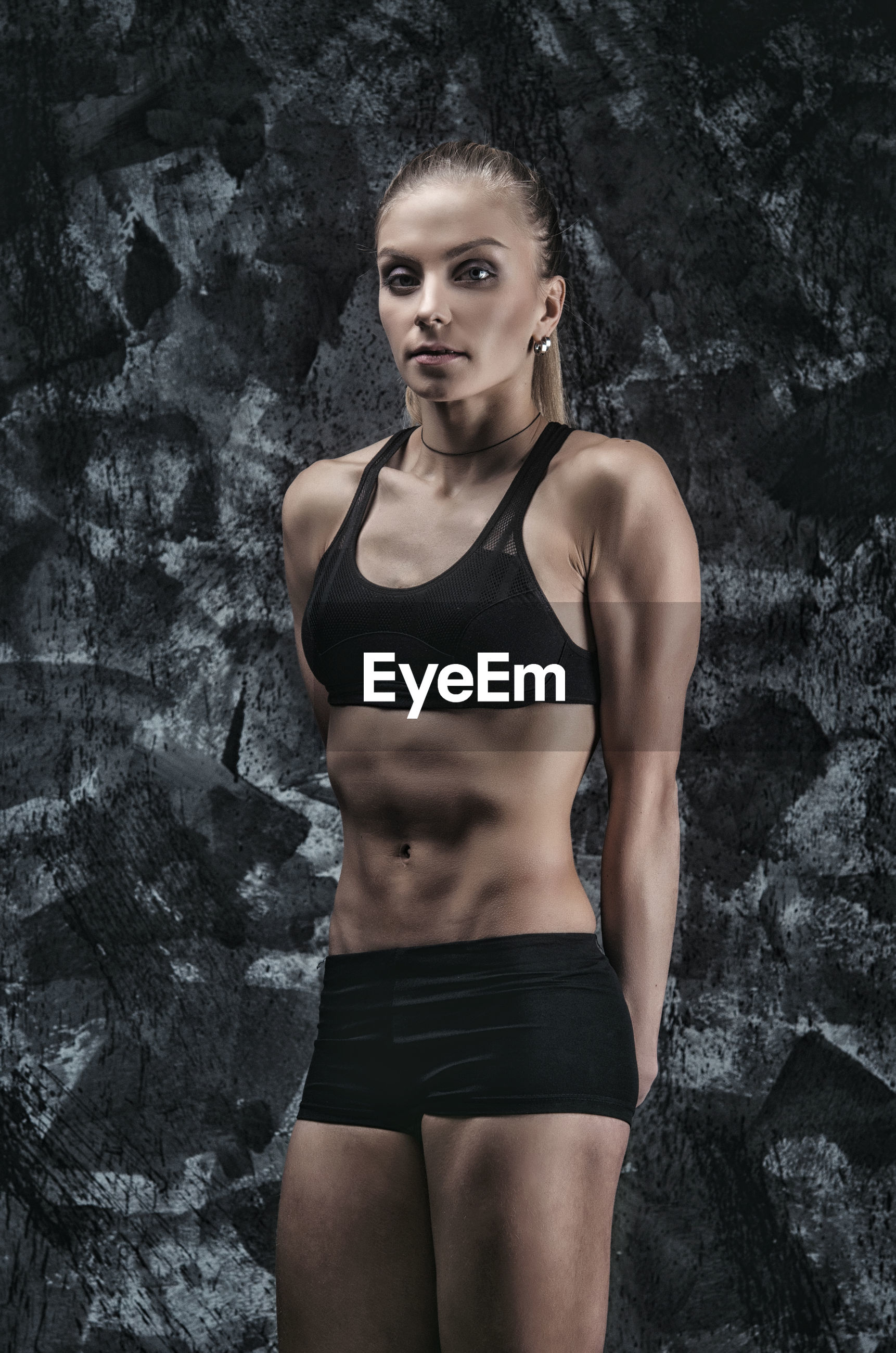 Female athlete in sports clothing standing against wall