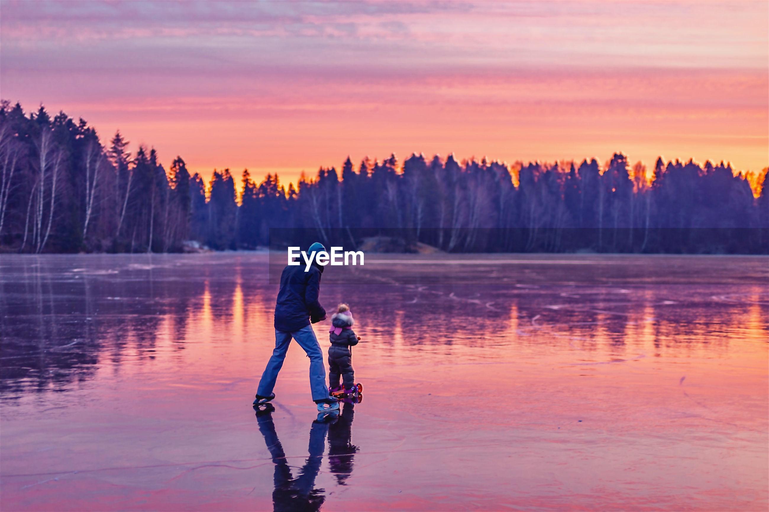 FULL LENGTH OF MAN STANDING ON LAKE AGAINST SKY DURING SUNSET