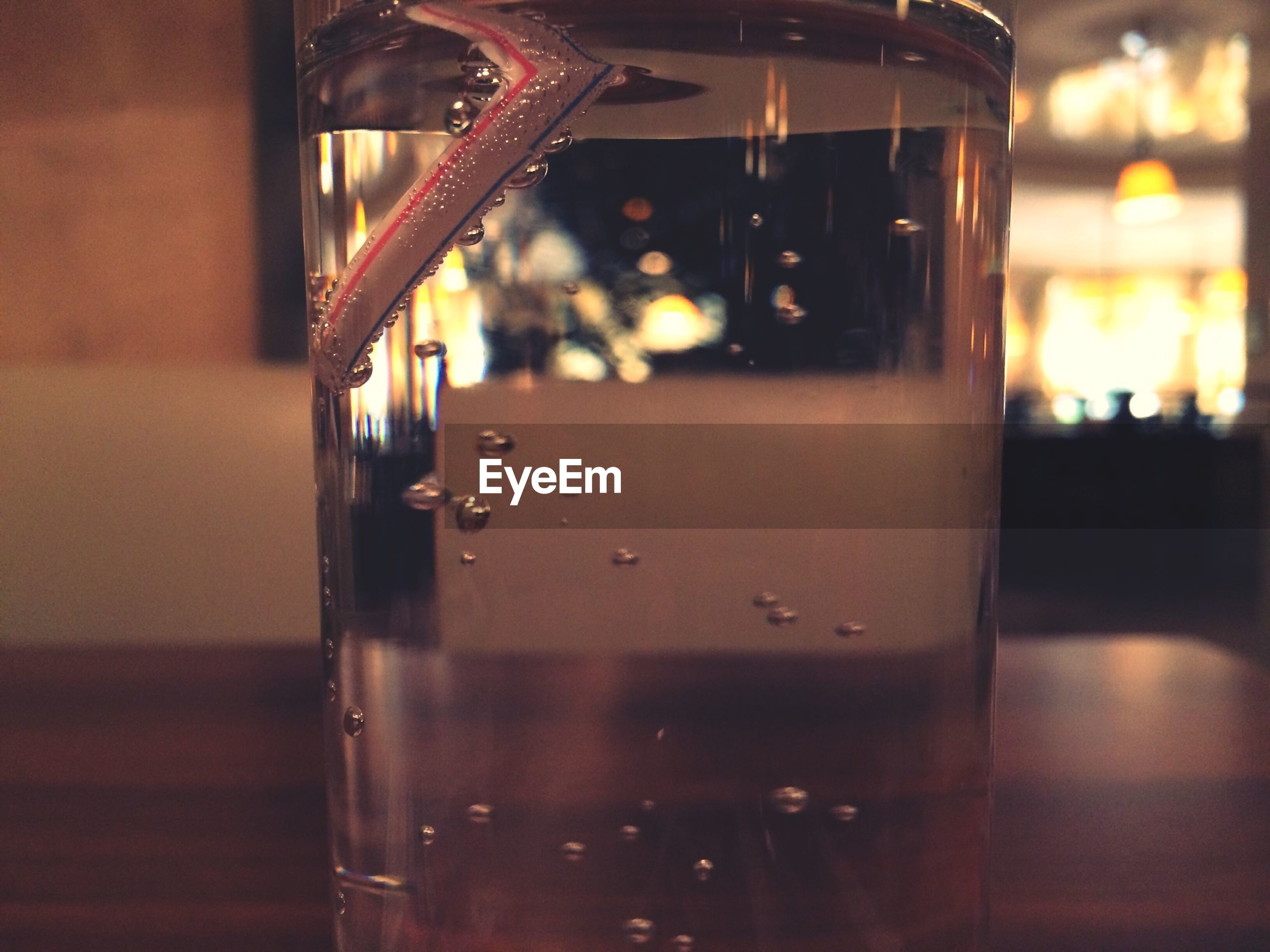 indoors, illuminated, focus on foreground, glass - material, night, transparent, close-up, reflection, no people, selective focus, window, lighting equipment, glass, wet, built structure, water, architecture, table, light - natural phenomenon, drinking glass