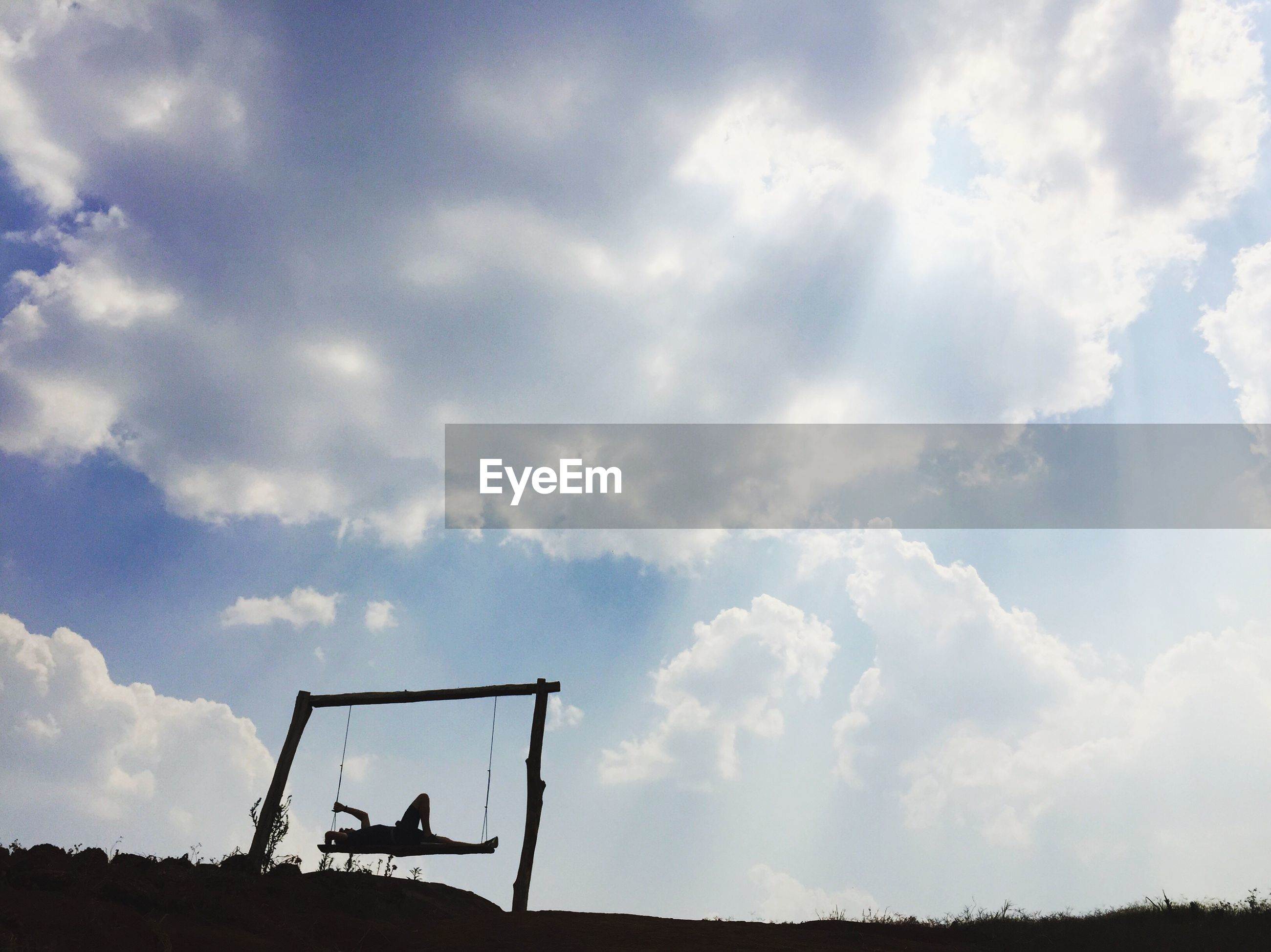 Low angle view of person lying on swing against sky