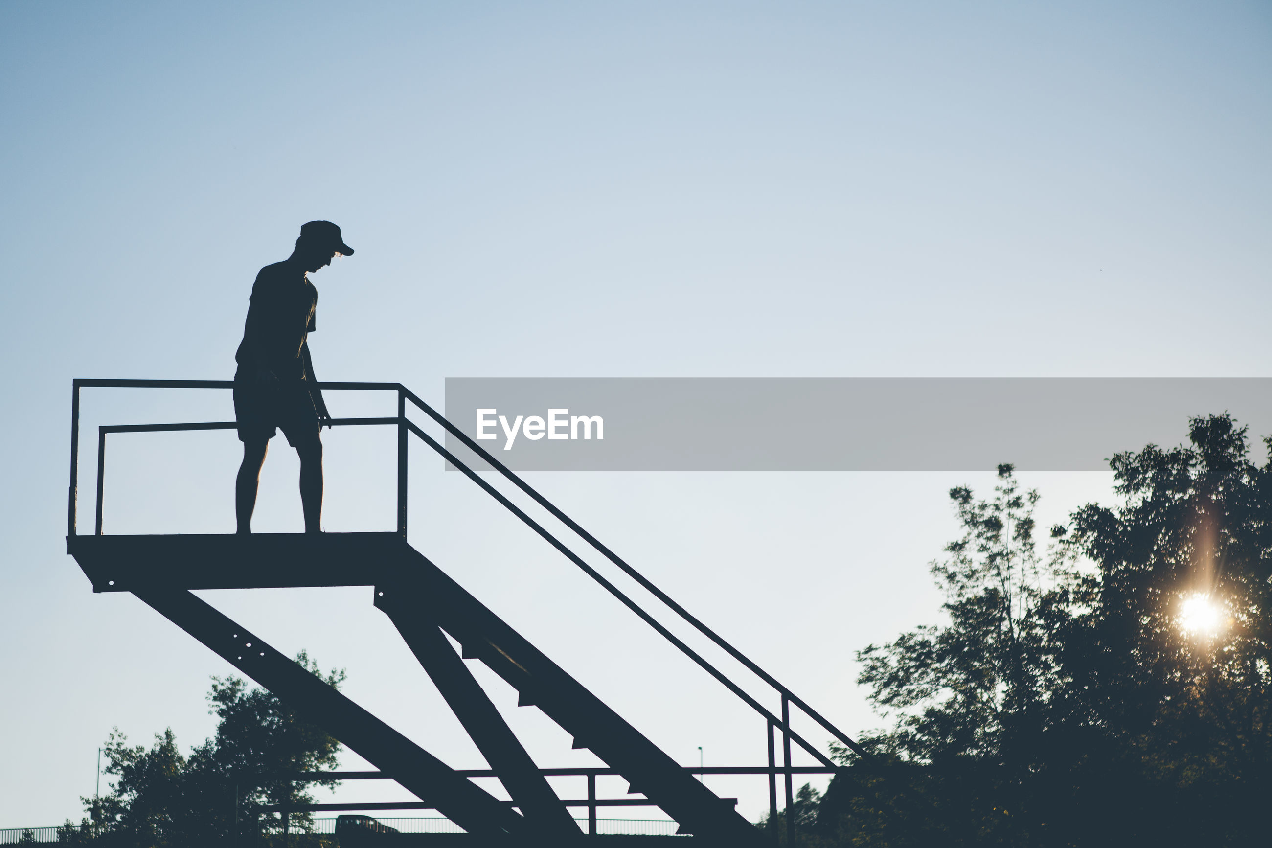 Low angle view of man on steps against clear sky
