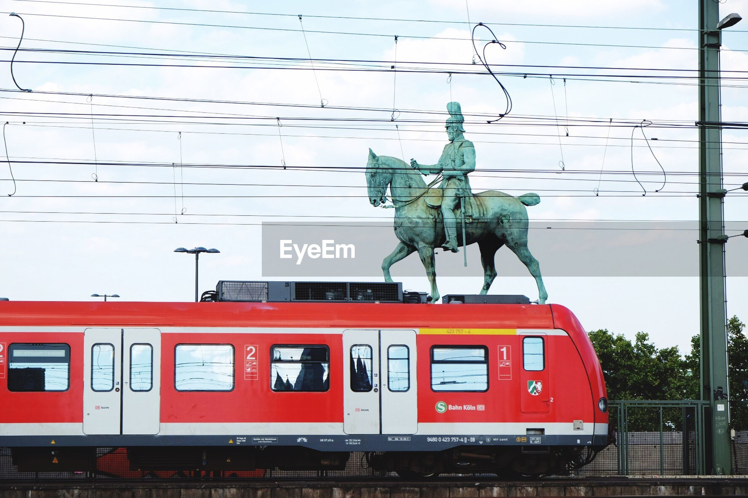 statue, art, sculpture, cable, art and craft, connection, horse, creativity, red, famous place, sky, power line, outdoors, cloud - sky, day, history, station, culture, arrival, monument, no people, symbol, office building
