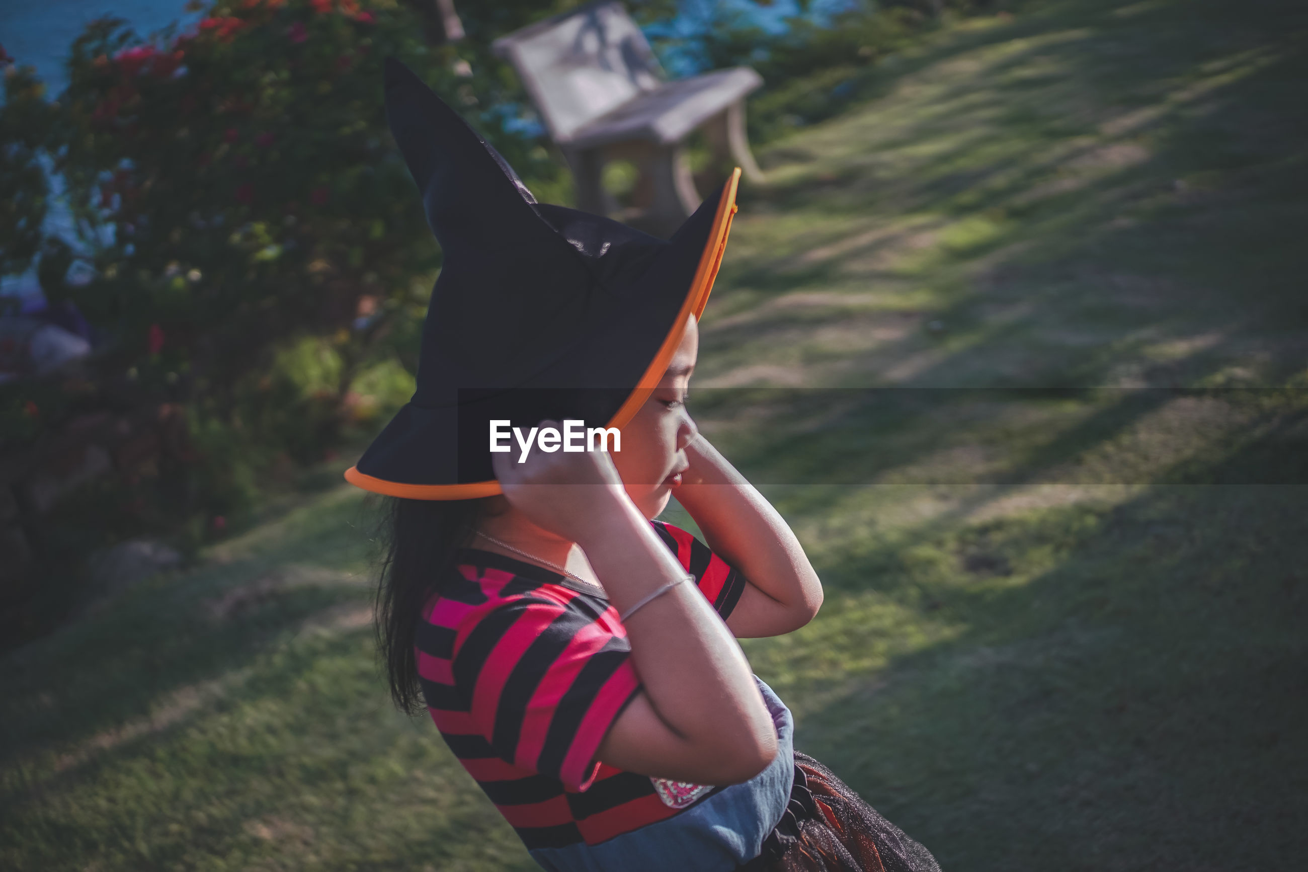 Side view of girl wearing witch hat on field