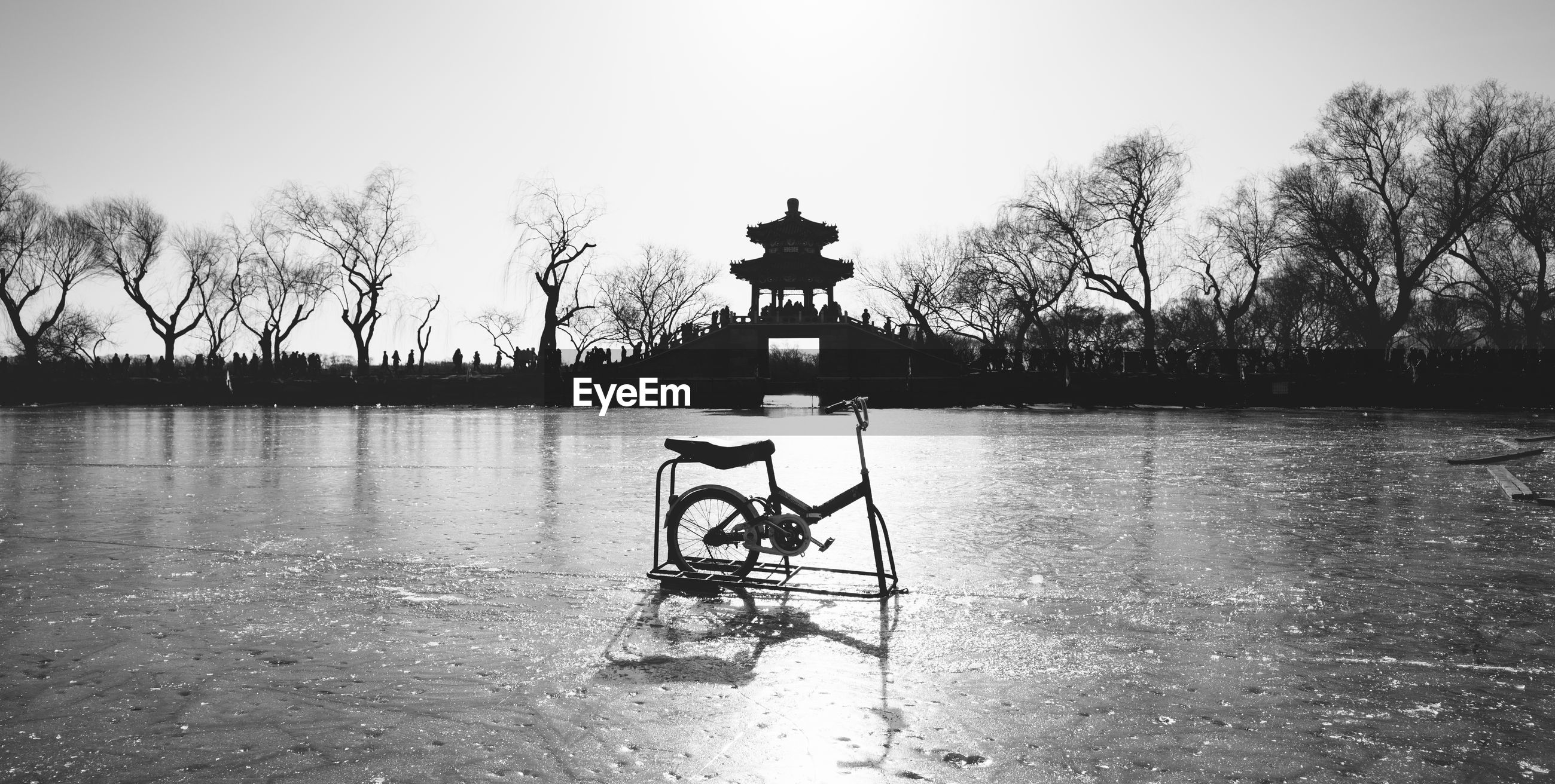 Bicycle on frozen lake against silhouette bridge