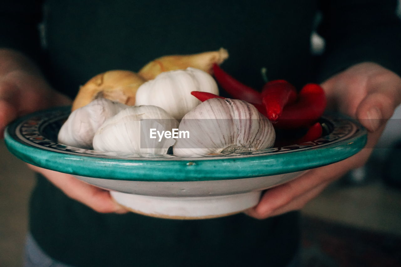 Midsection of person holding ingredients in bowl at home